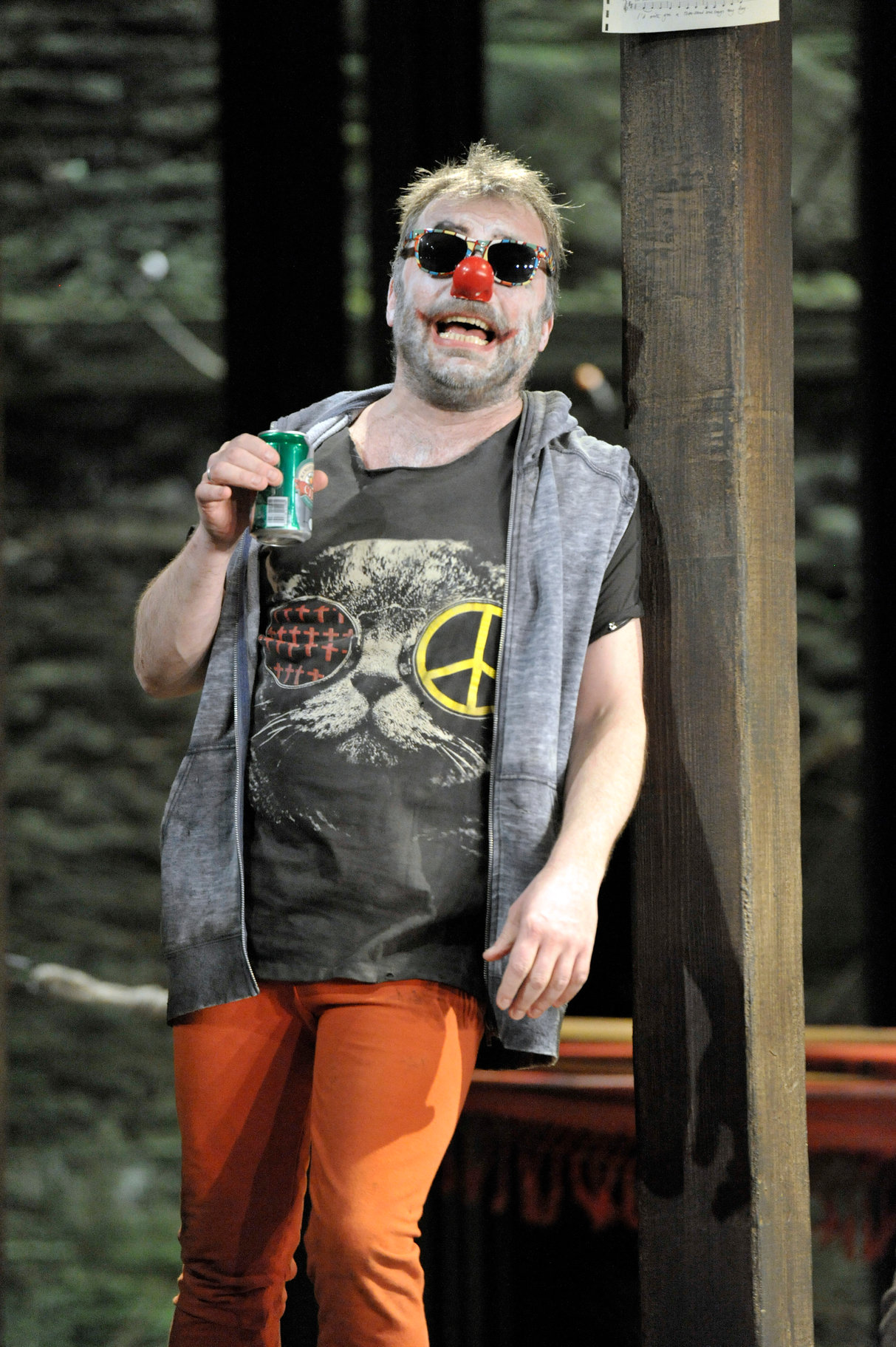 A scruffy man in sunglasses and a red nose.