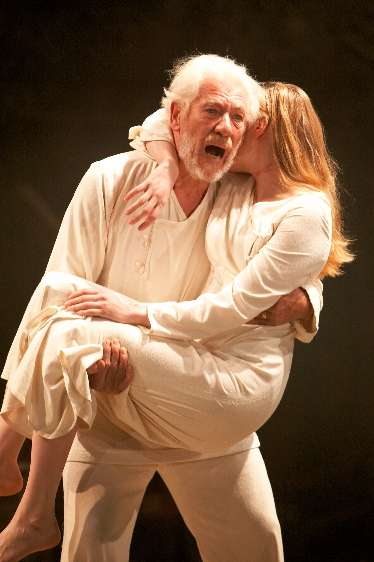 An older man in white carries the body of a young woman.
