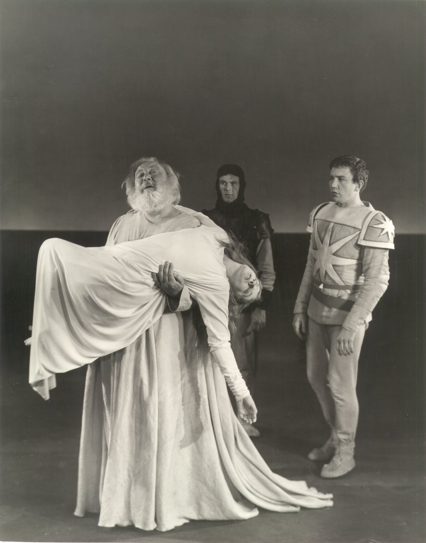A man in a white robe carries a young woman's body.