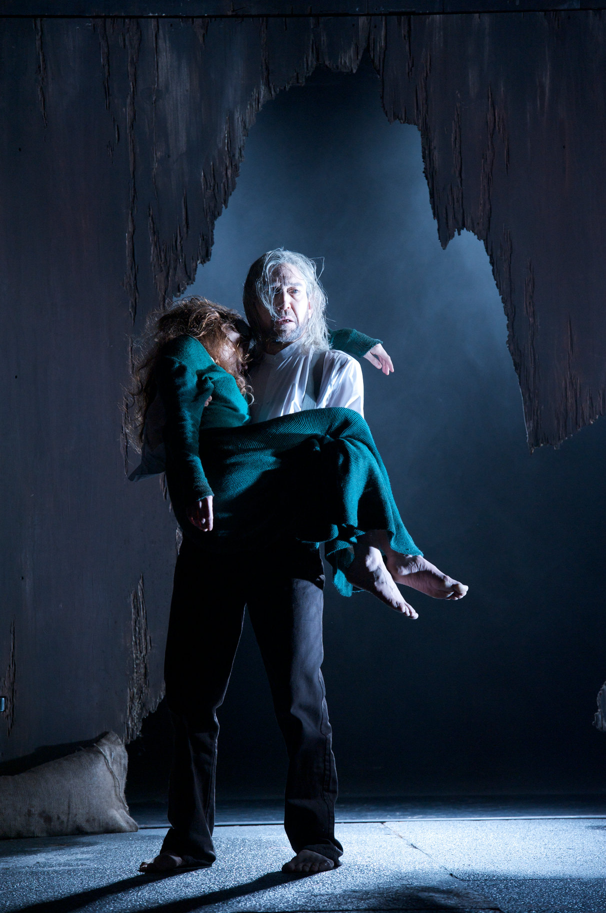 A man carries a woman's body through a cave.