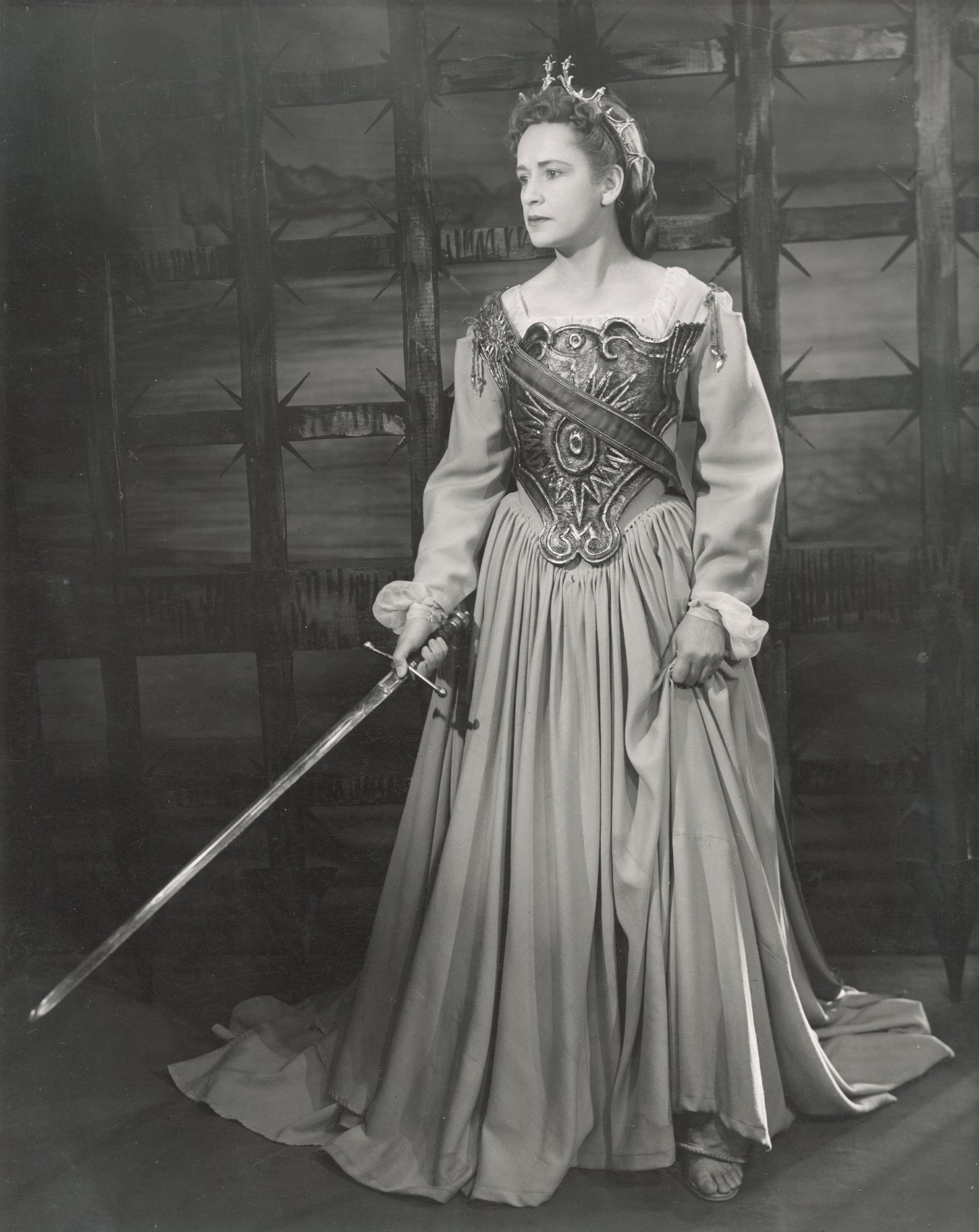 A woman in a dress and armoured chestplate holds a sword.