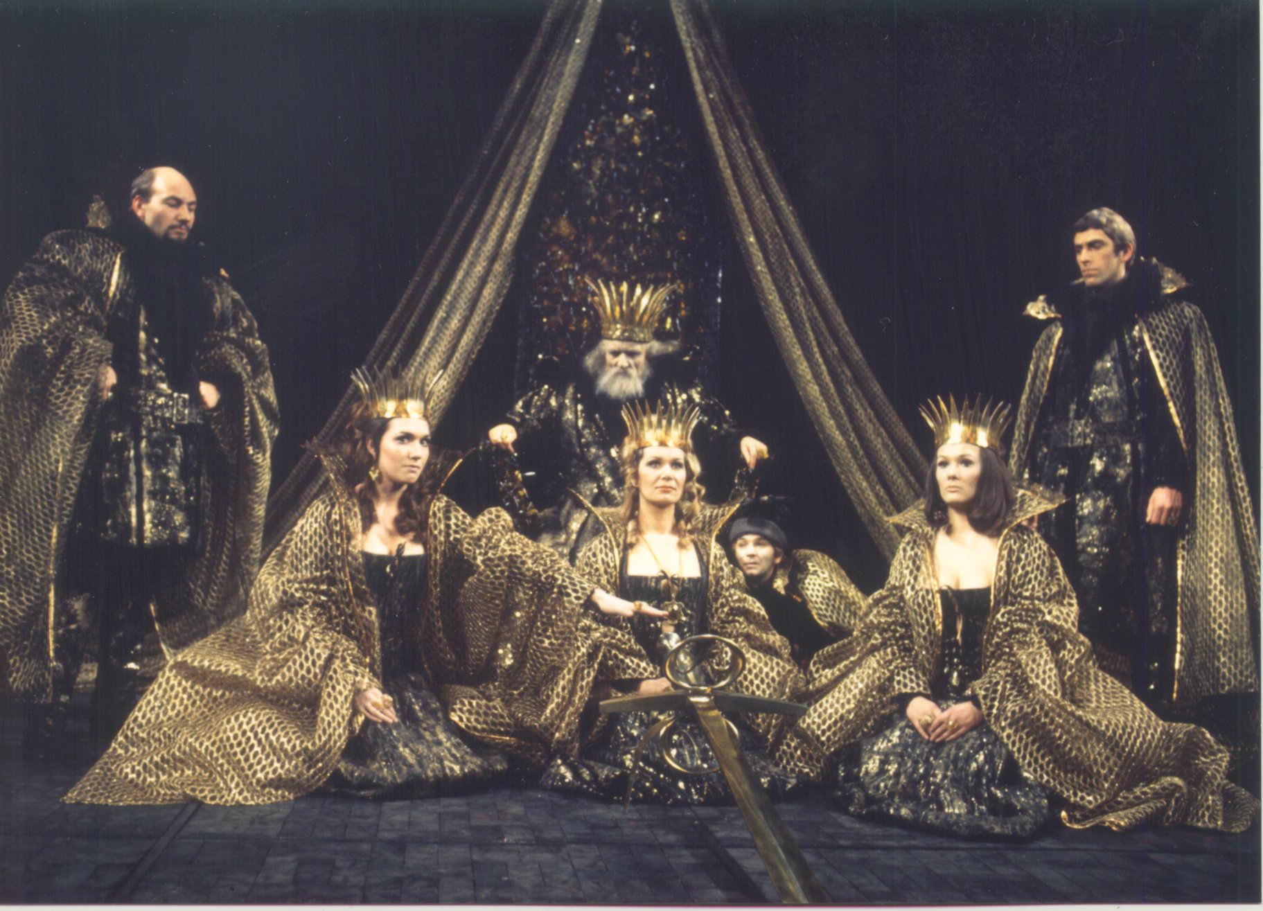 Three women in gold kneel in front of a king on his throne.