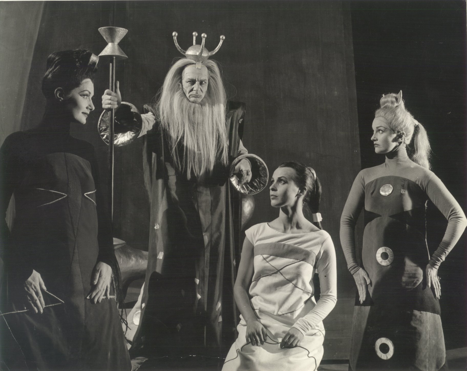 Three women in smock-style dresses stand in front of a bearded man with a crown and sceptre.