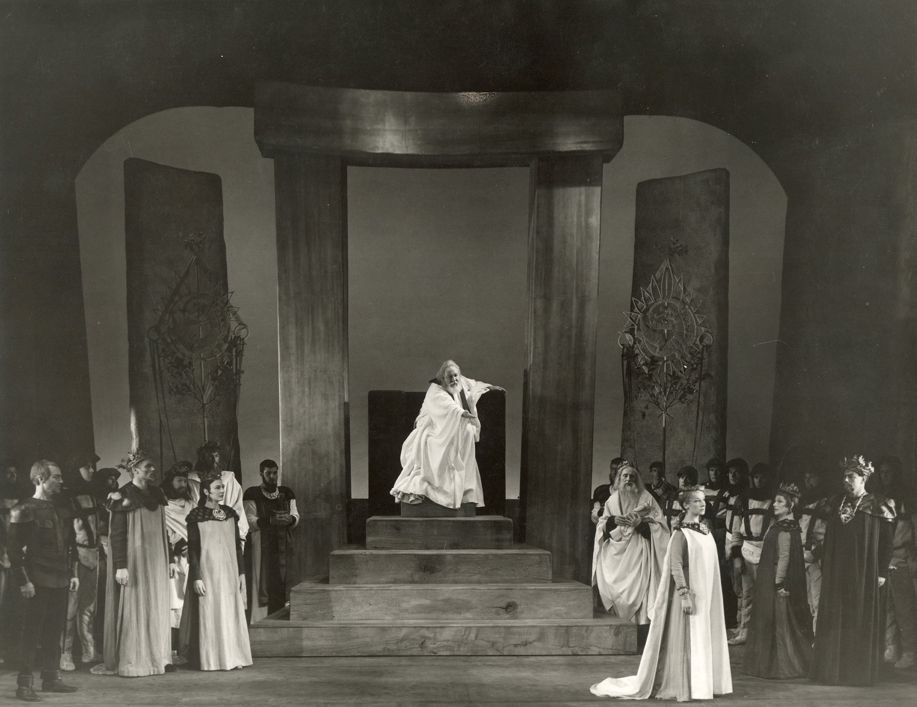 A king presides over his court, pointing an accusative finger at a woman walking away.