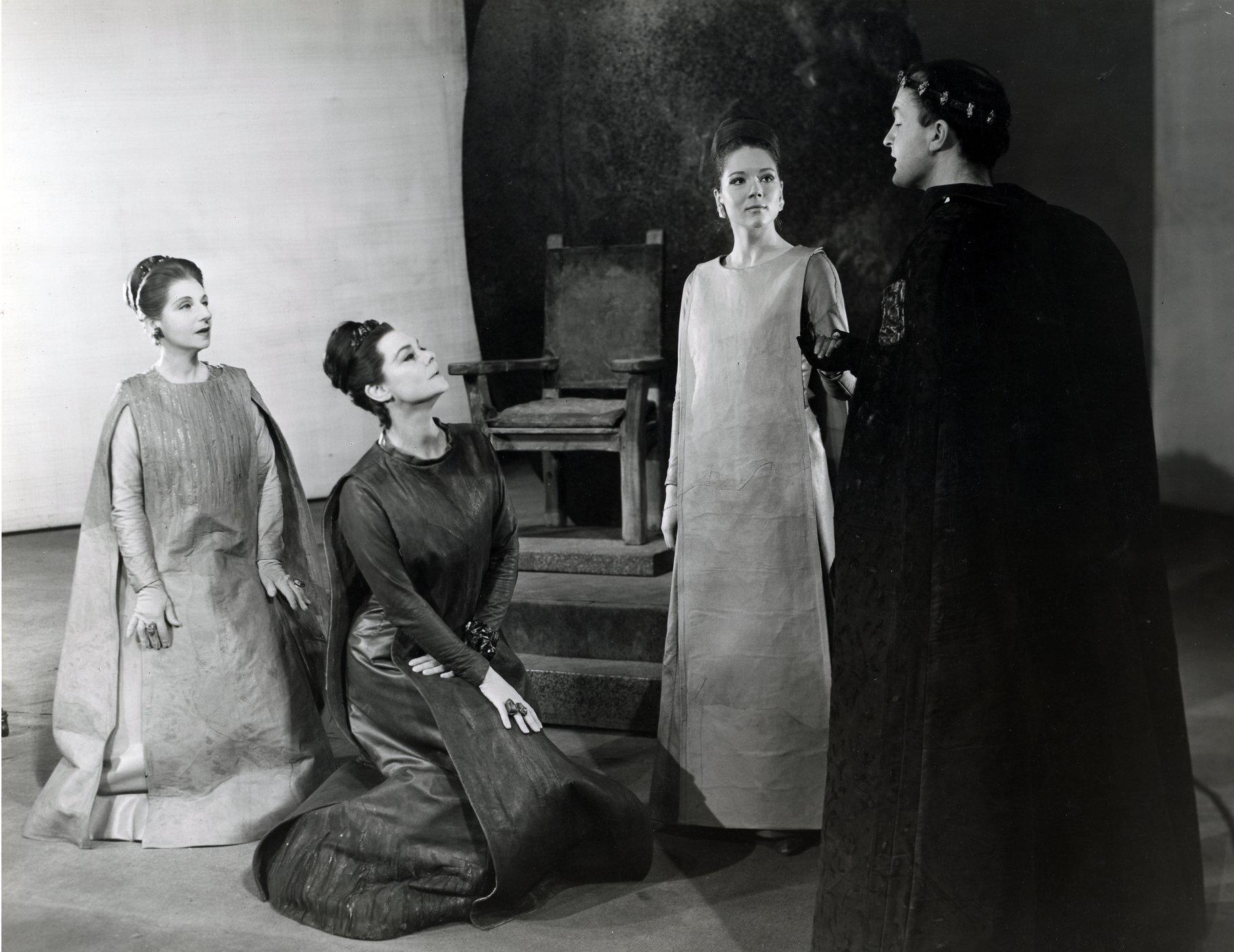 Three women listen to a man in robes talking.