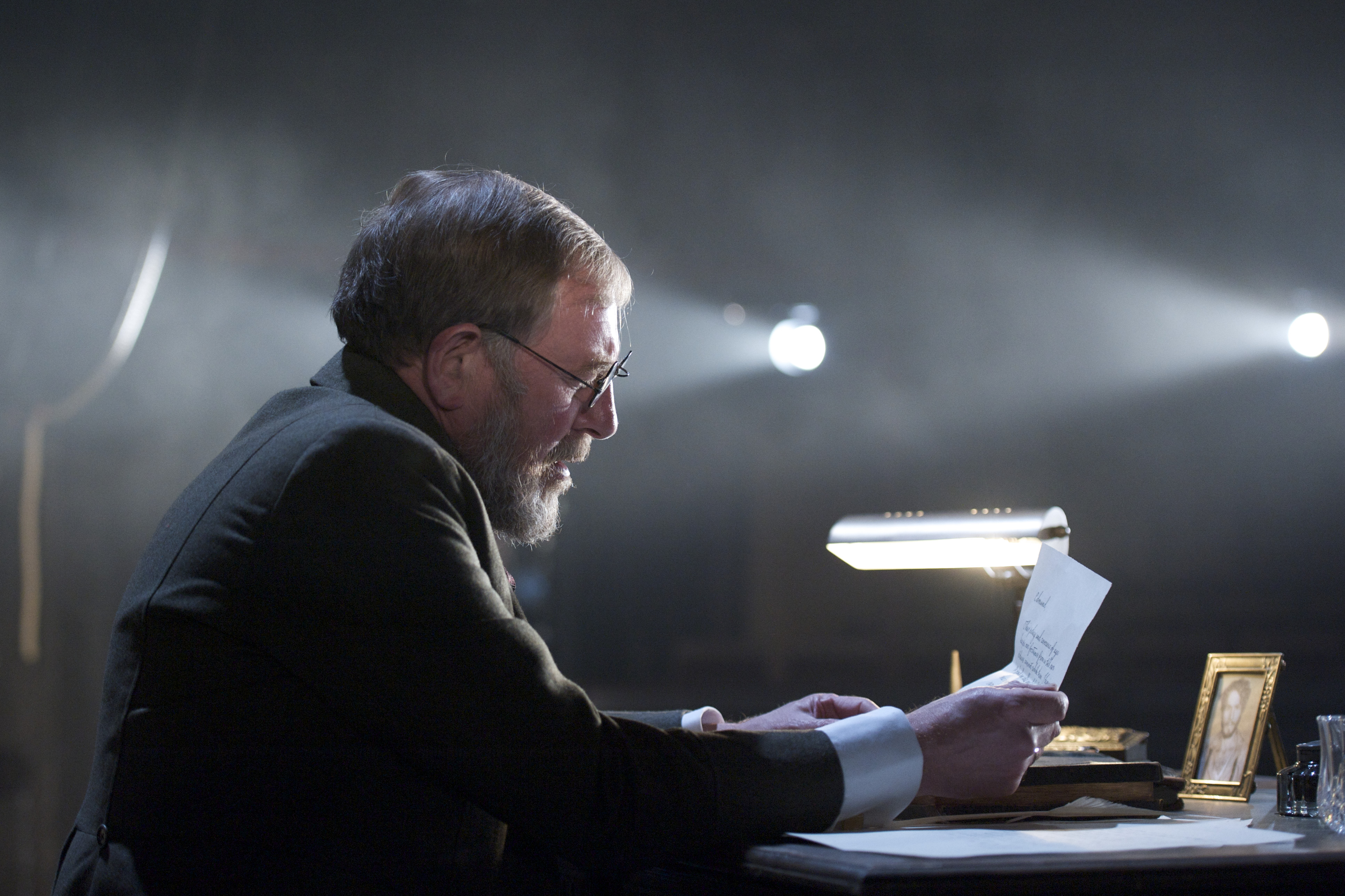 A man reads a letter at his desk.