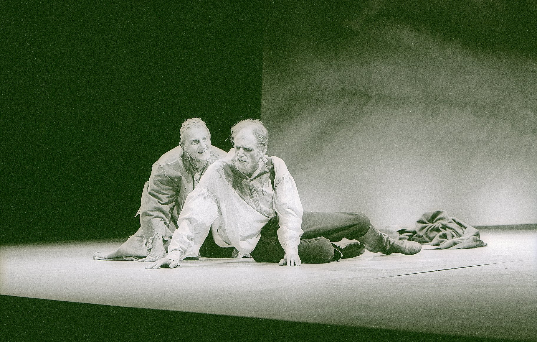 Two men lie near the edge of the stage.