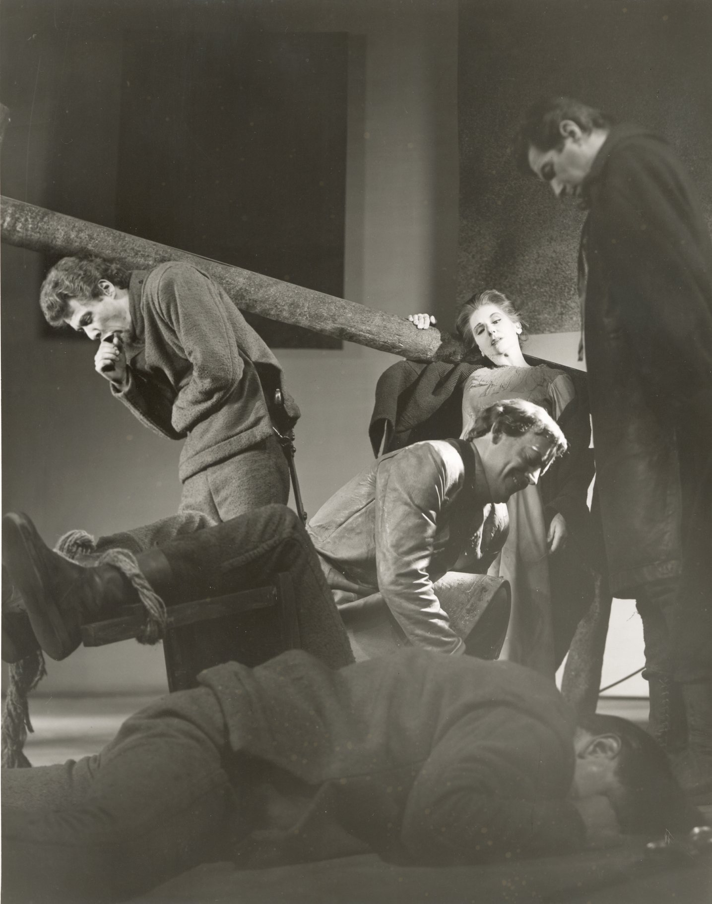 A man lies on the floor rubbing his eyes as others stand over him.