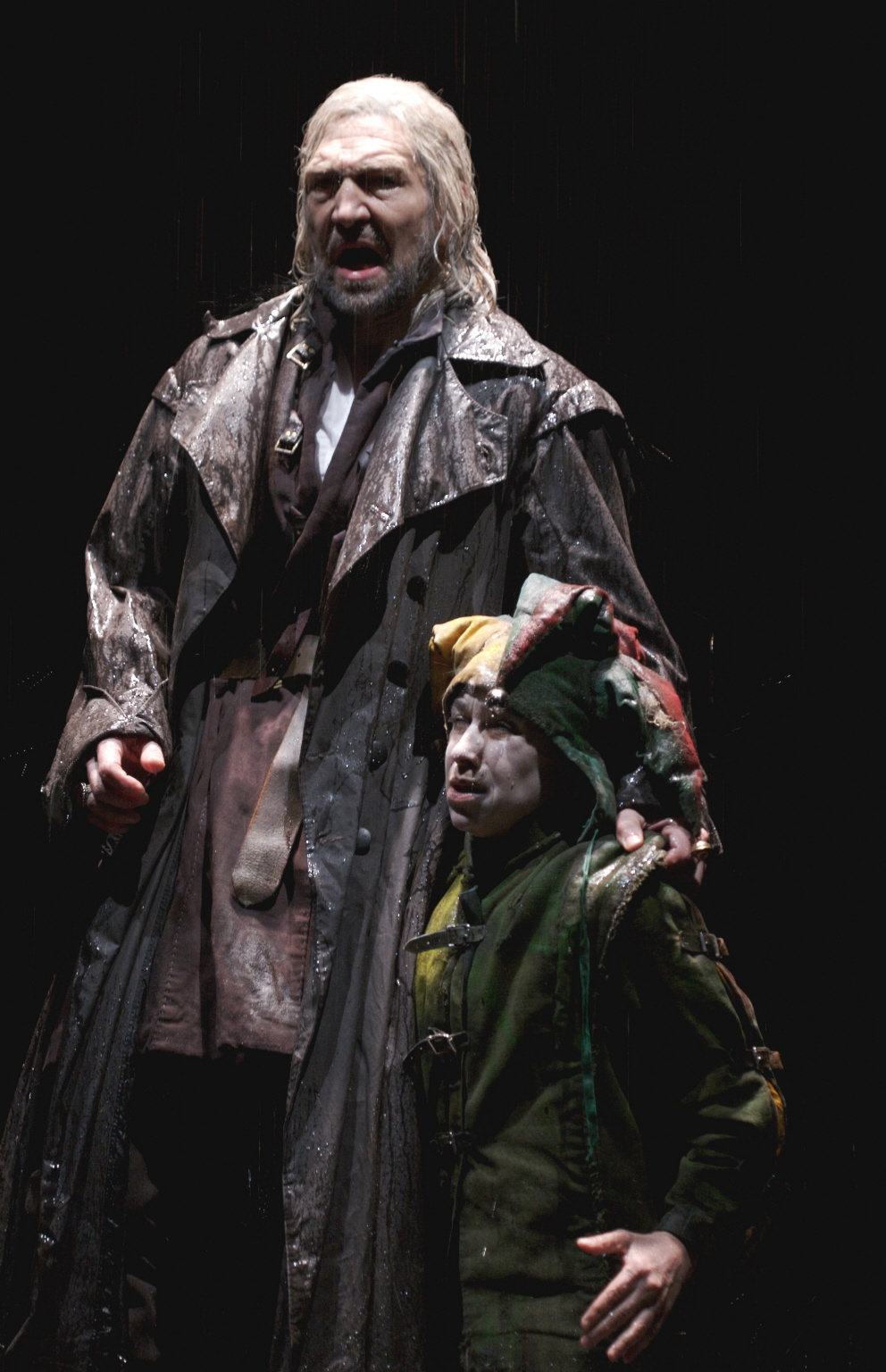 A jester kneels at the side of a man in a long black greatcoat.