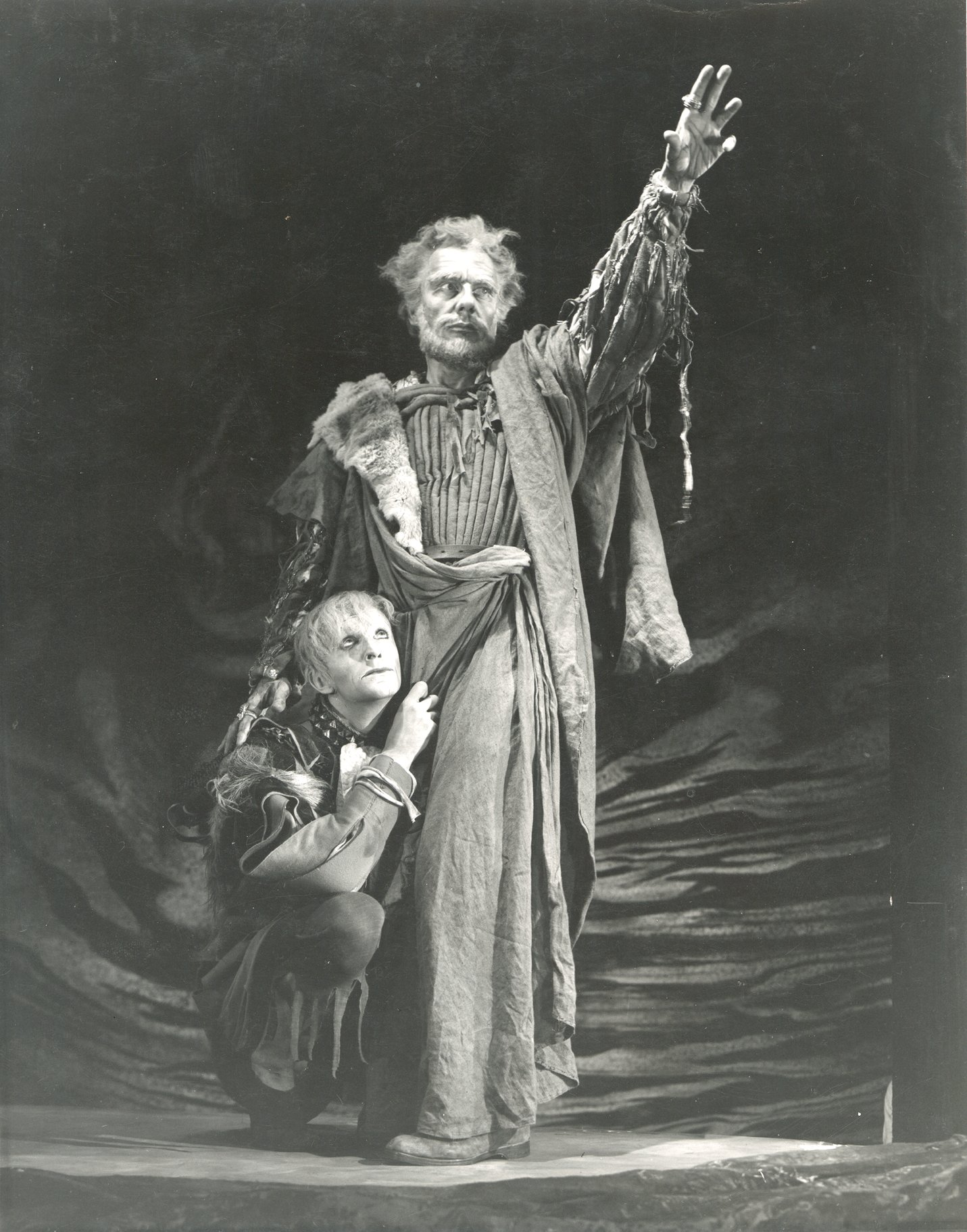 A man clutches at the robes of an older man who stands above him.