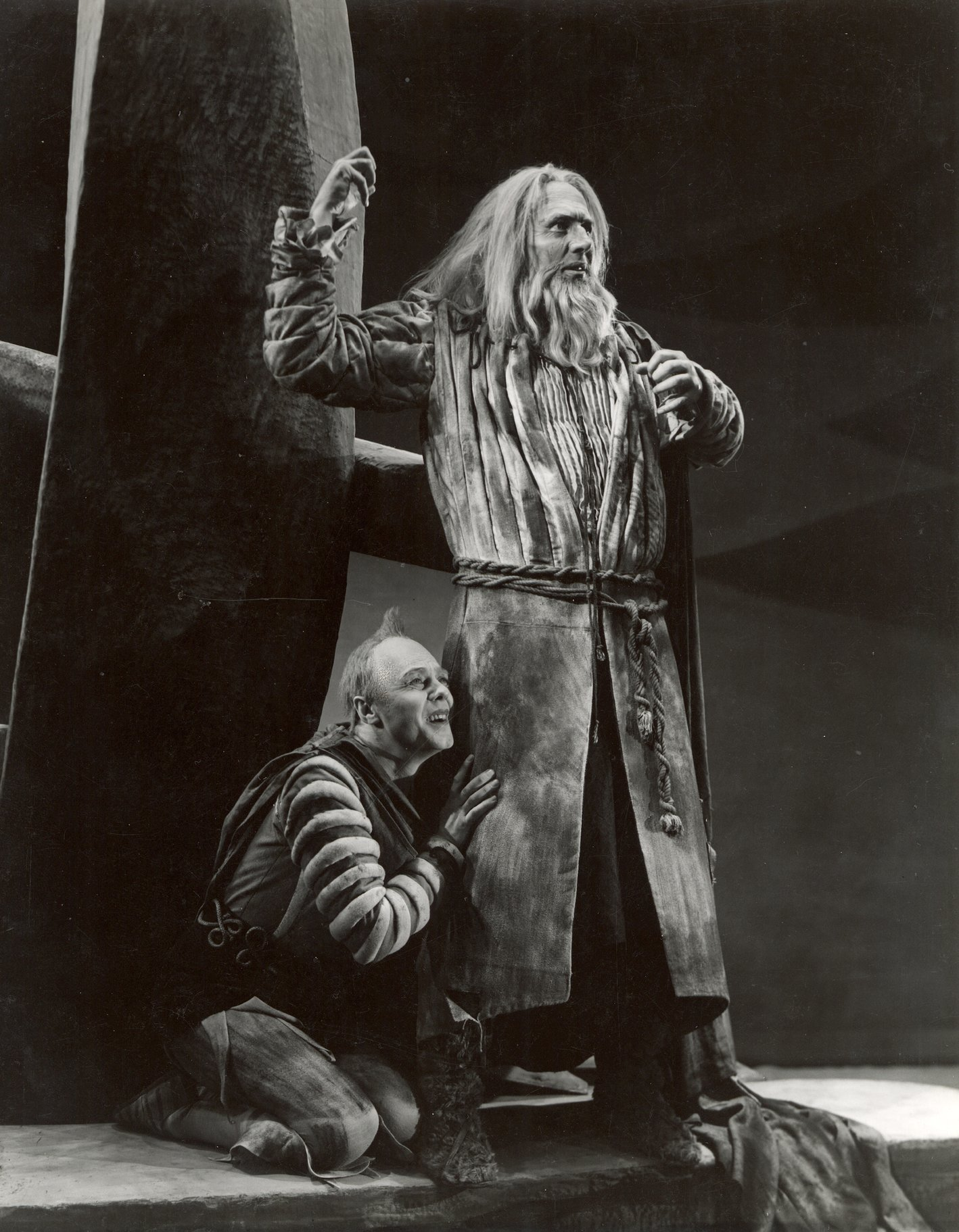 A man kneels at the side of a man in a long coat.