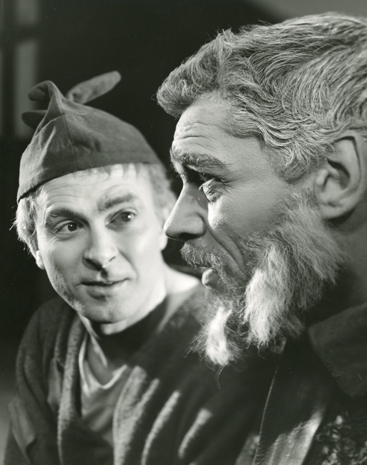 A man in a cloth cap talks to an older bearded man.