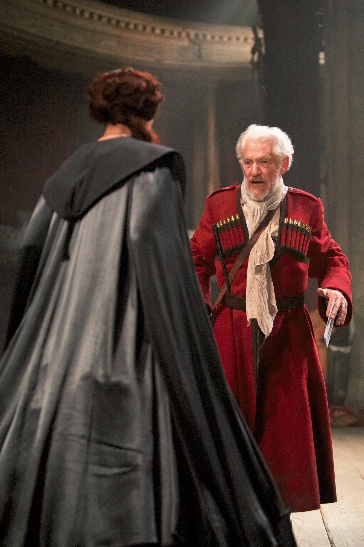 A man in a red greatcoat talks angrily to a woman in a long robe who stands with her back to camera.