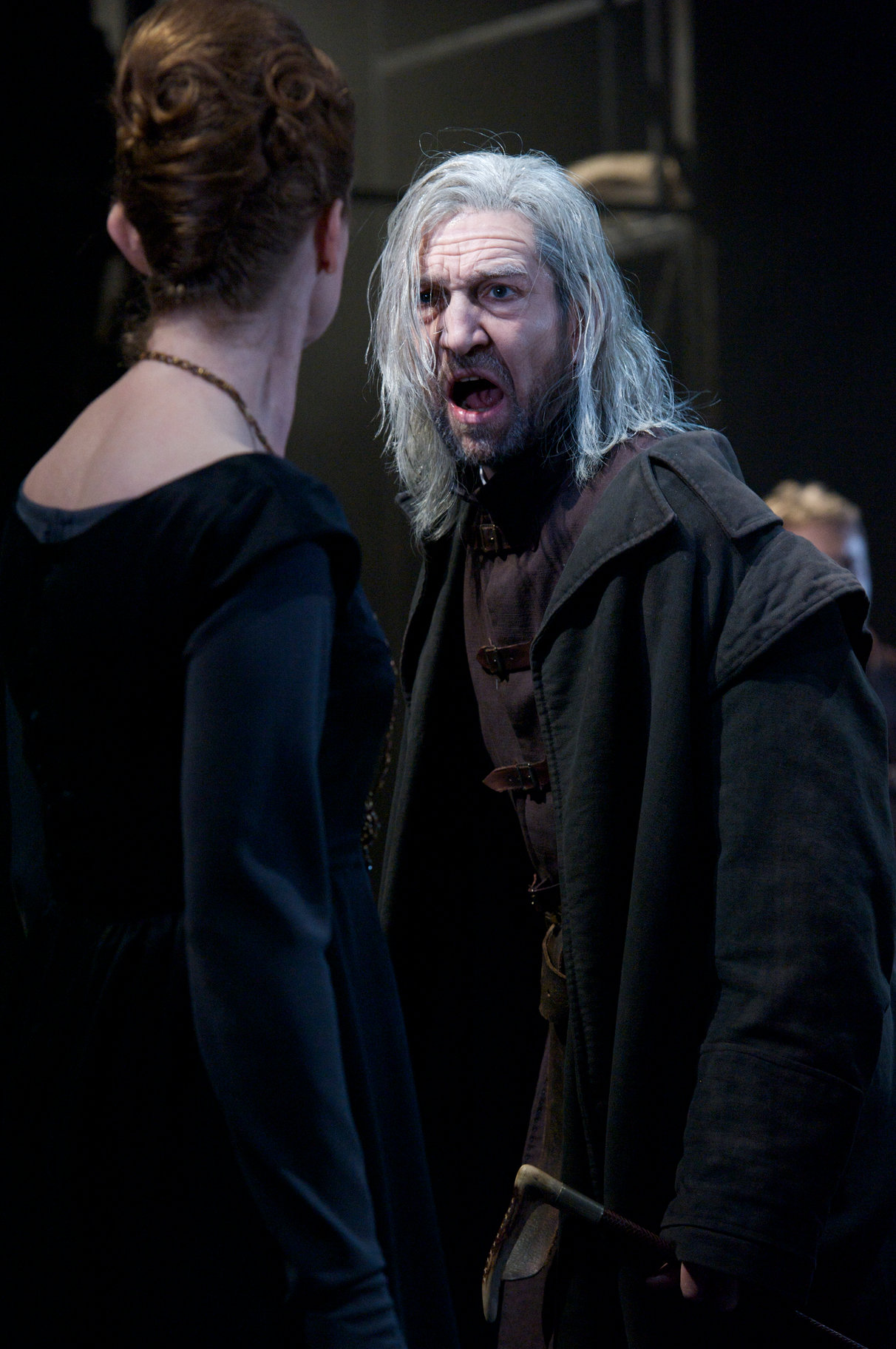 A man in a black coat with wild white hair shouts at a woman in a midnight blue dress.