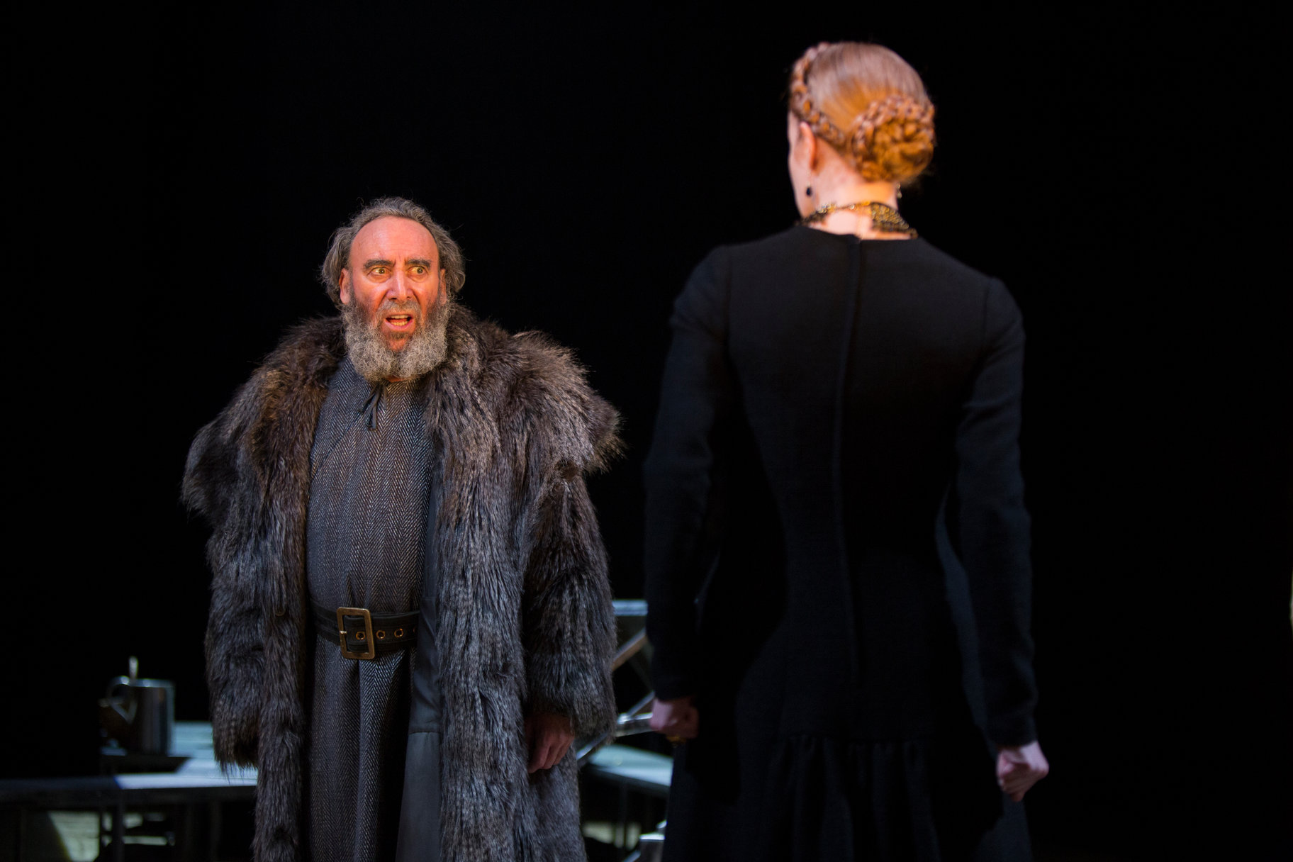 A man in furs talks angrily at a woman in a black dress.