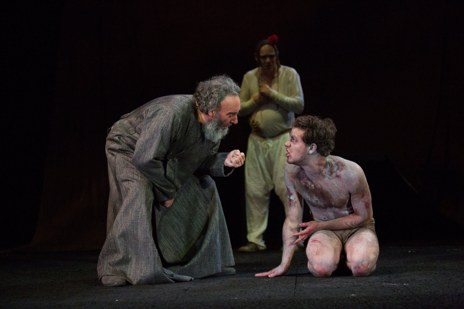 A man in a grey robe bends over a younger bare-chested man who is covered in paint.