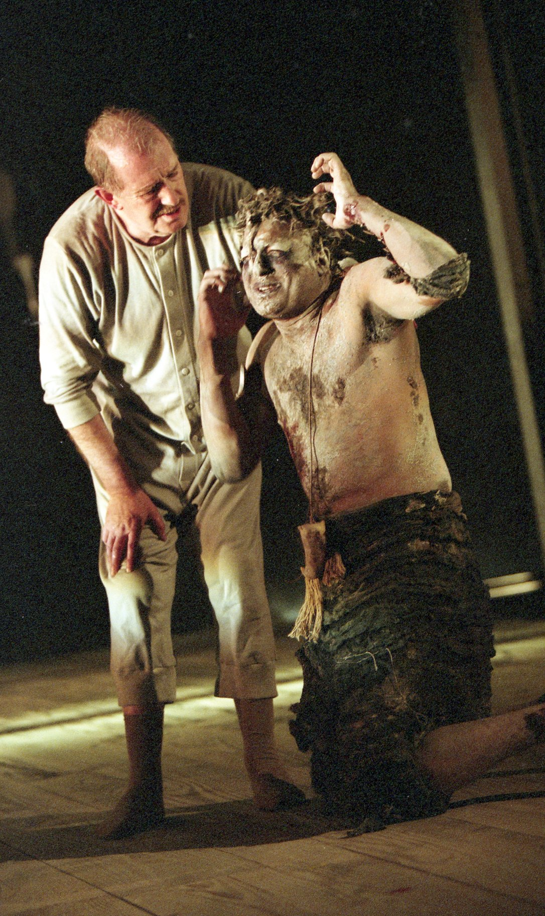 A man in long johns grips the neck of a man covered in mud and leaves.