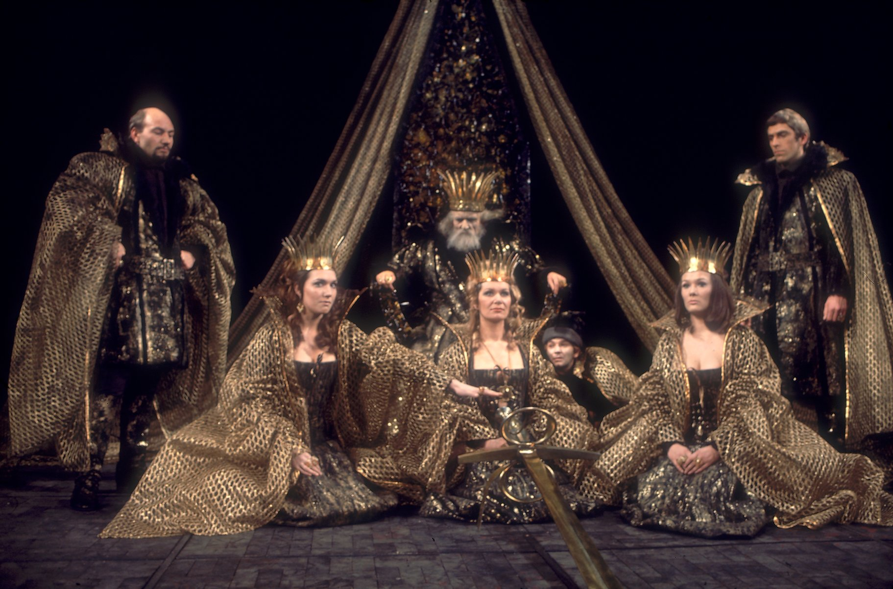 Three women in gold sit in front of a king on his throne.