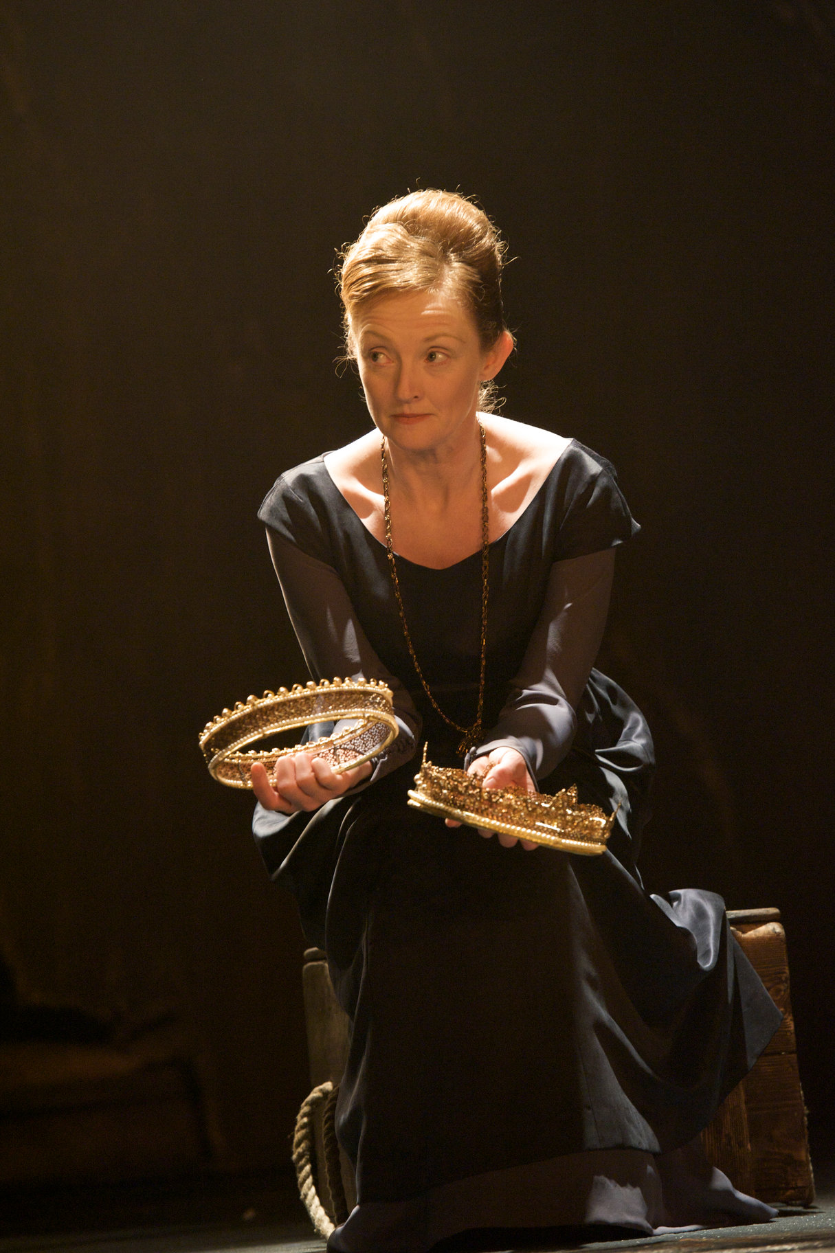 A woman in black holds two crowns.