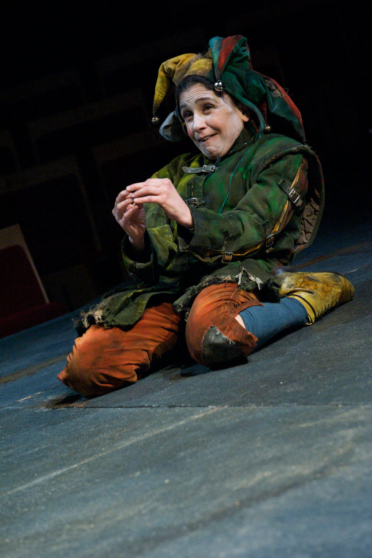 A jester kneels on the floor in multicoloured clothes.