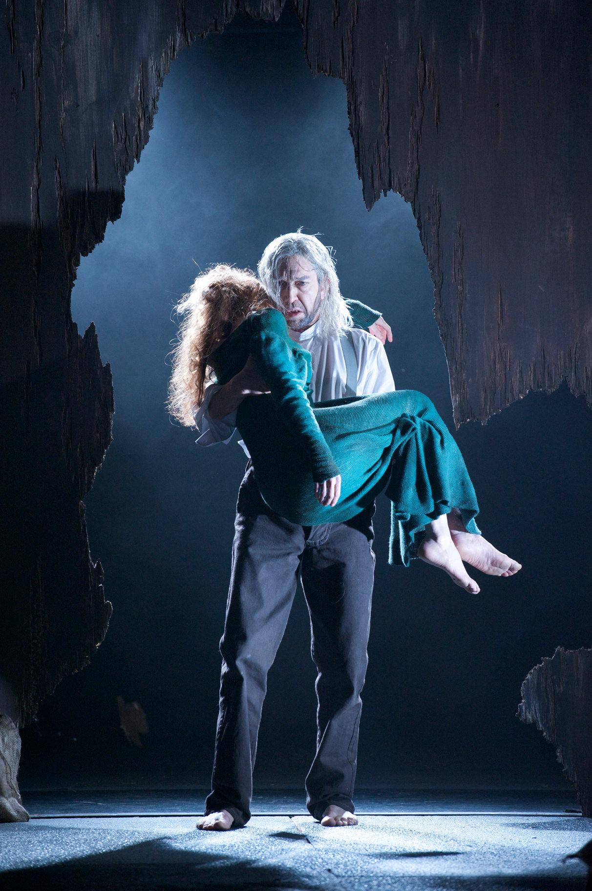 A man carries the body of a woman through a cave.