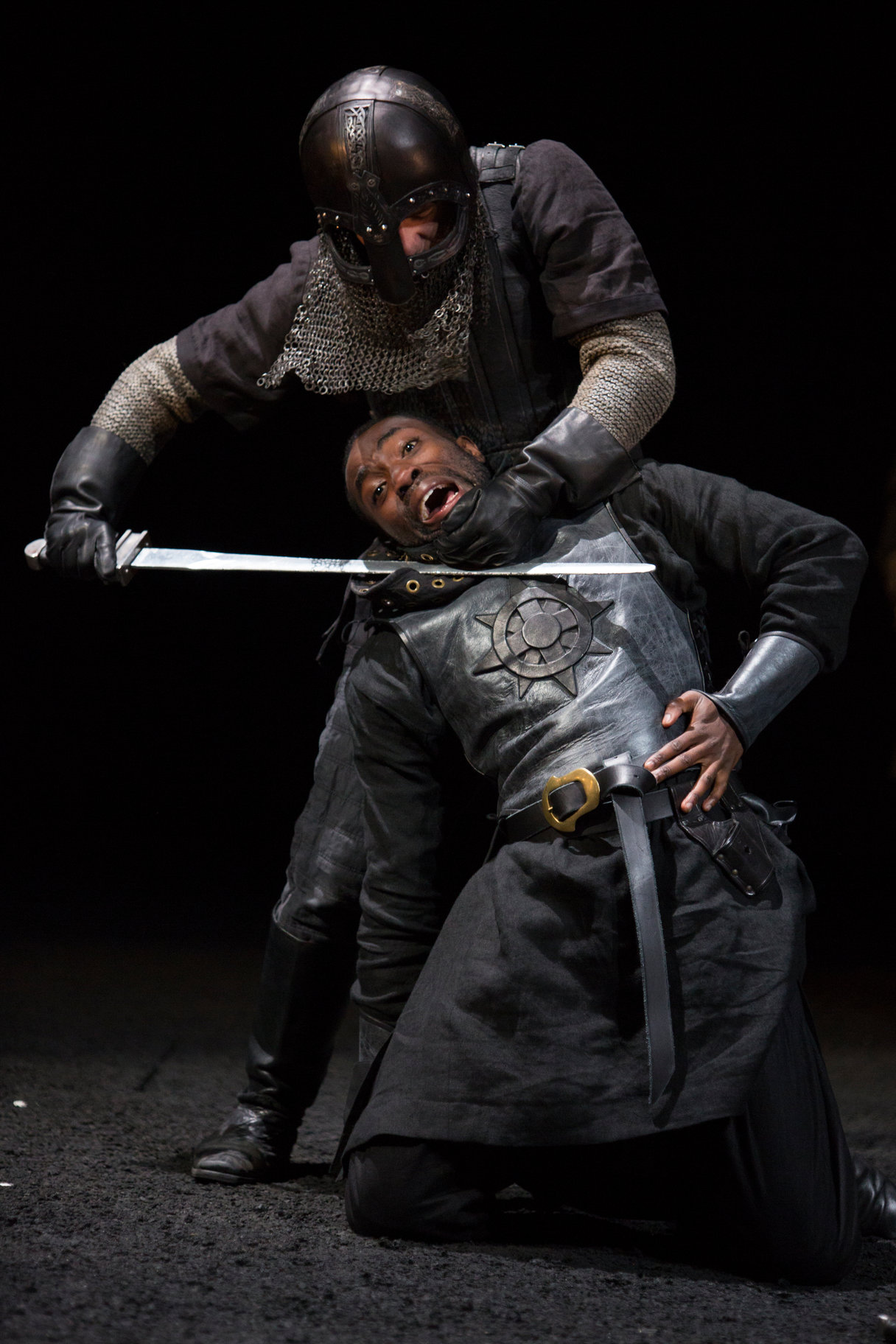 A knight in full armour holds a sword to a man's throat.