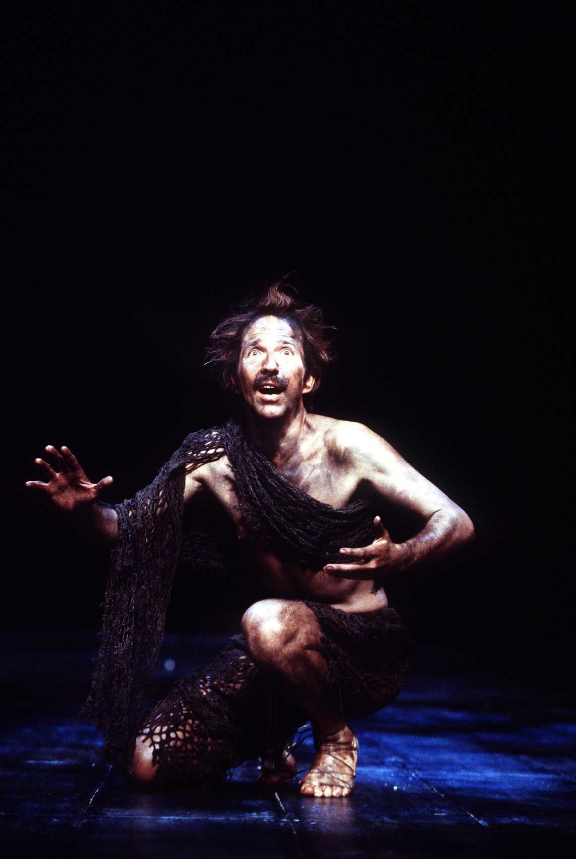 Edgar dressed as Poor Tom in rags and dirt, kneeling on the floor in the 1999 production of King Lear