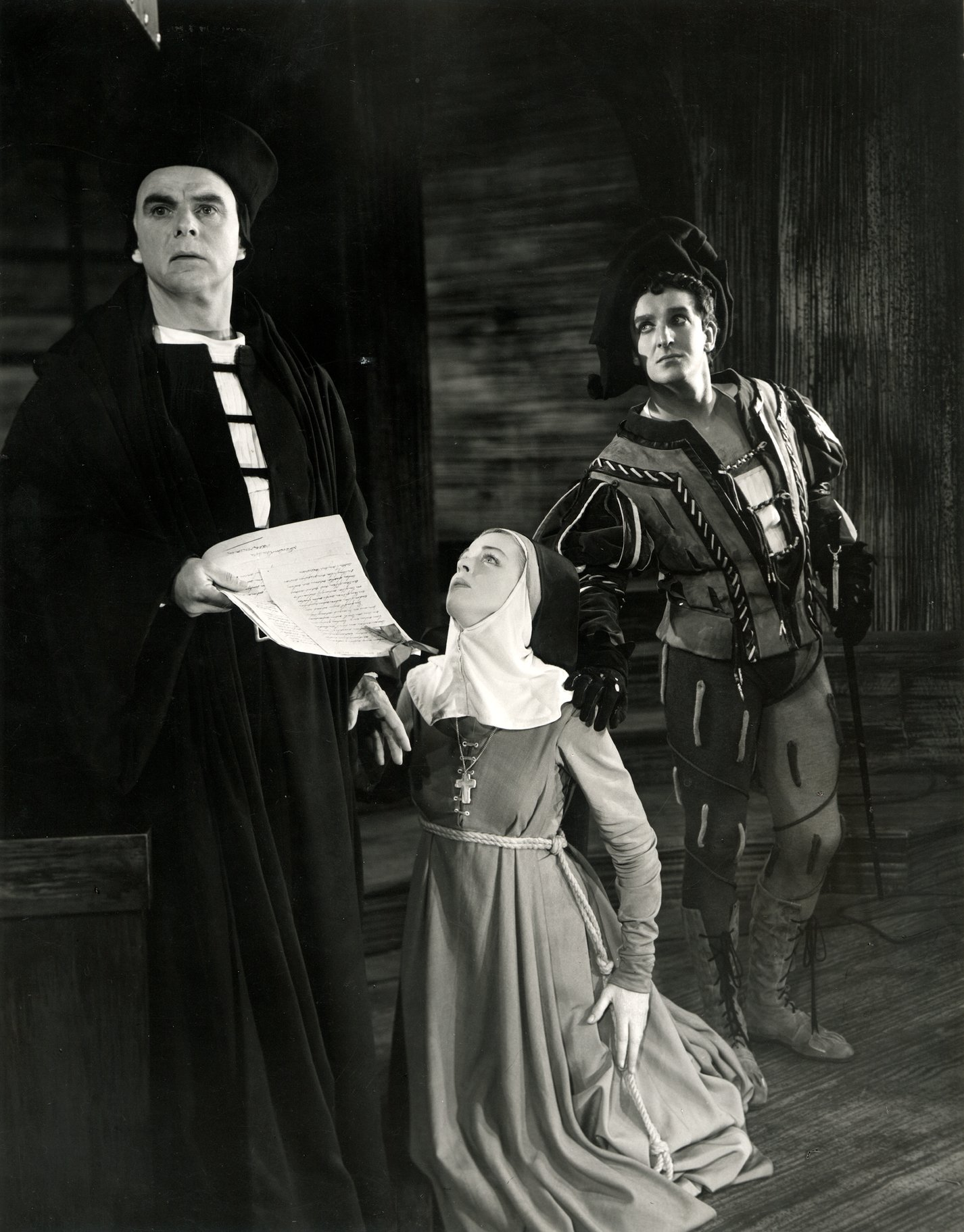 A woman kneels at the side of a man, as another man puts a warning hand on her shoulder.
