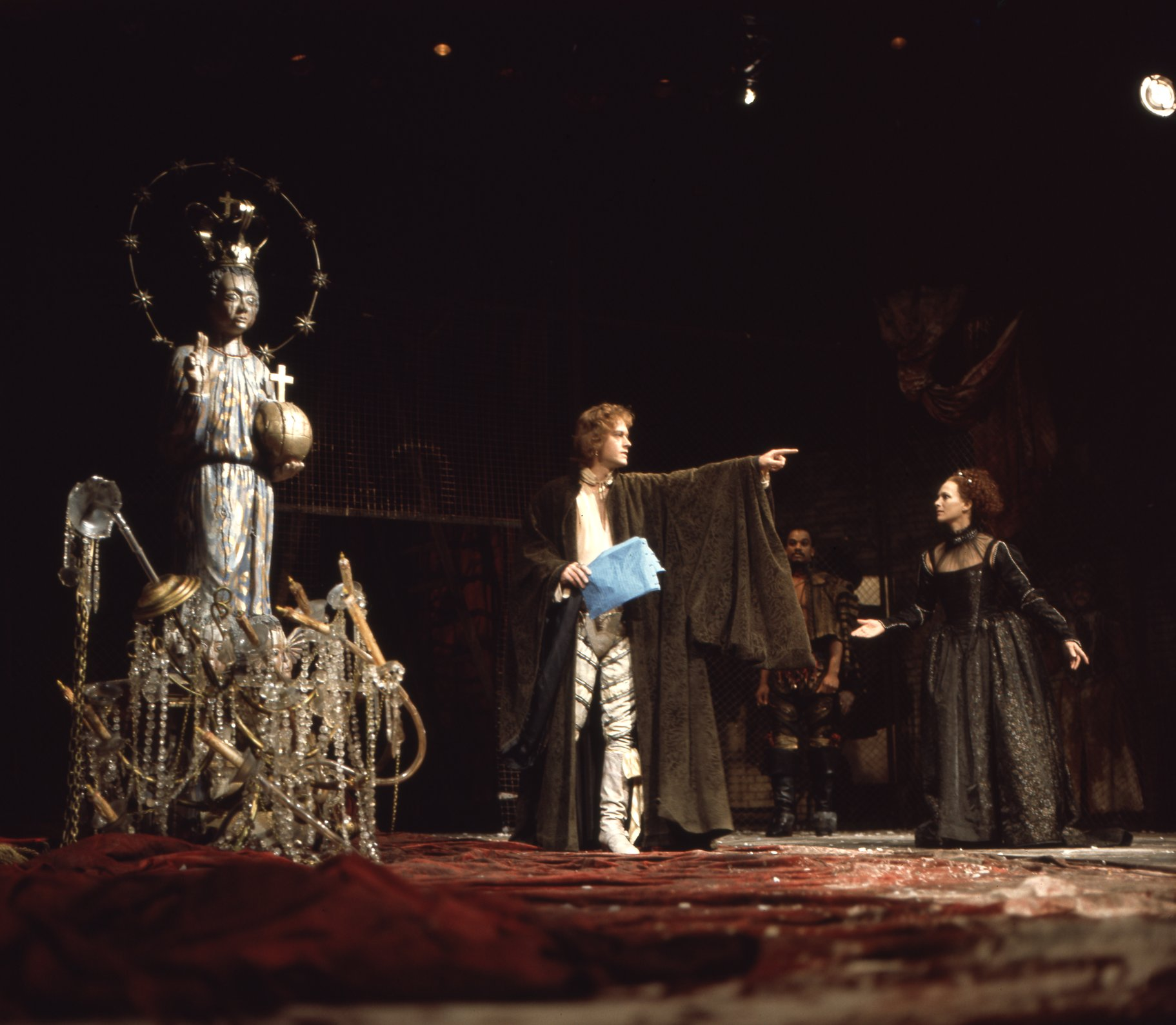 A man points away from a woman in a black gown.