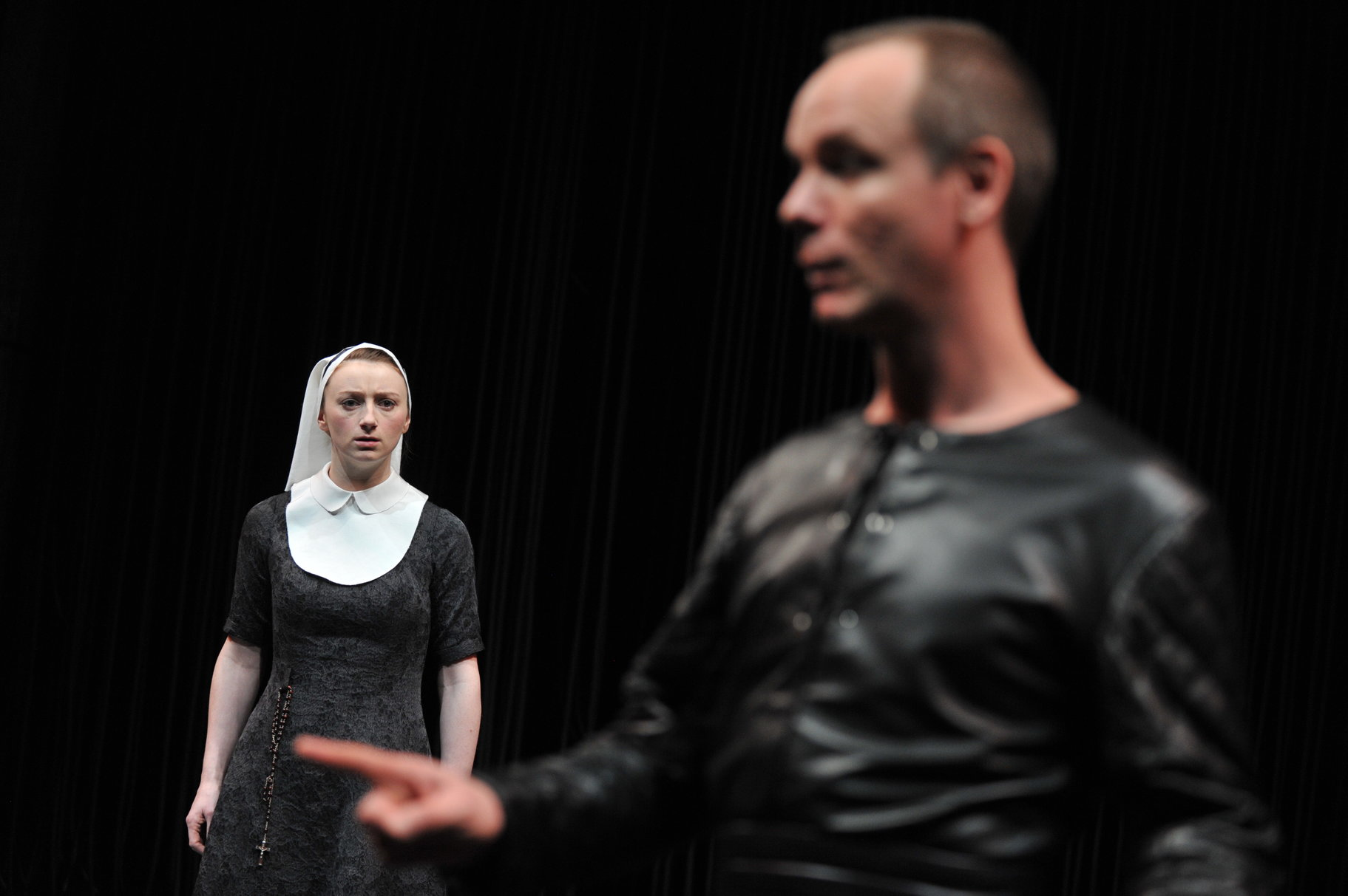 A nun looks accusingly at a man in black.