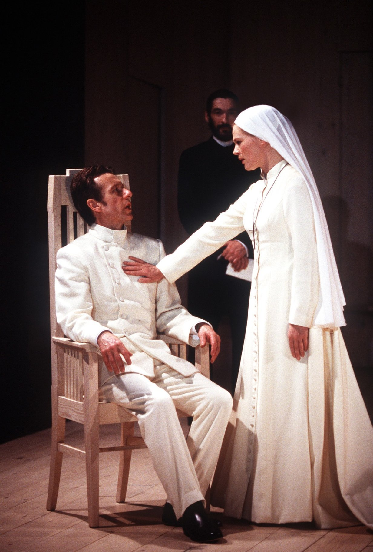 A woman in white puts a warning hand against a seated man's chest.