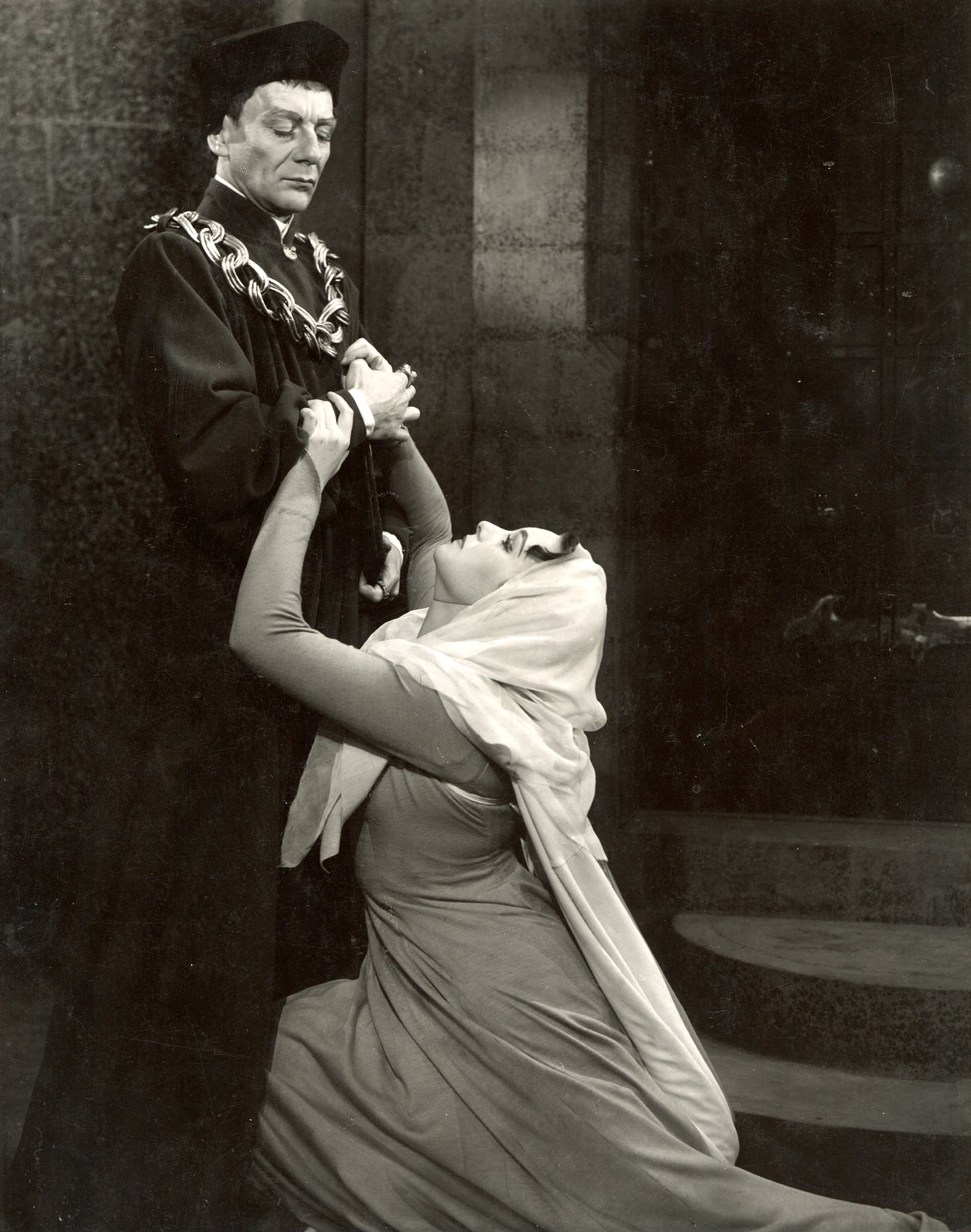 A woman pleads at the feet of an austere man.