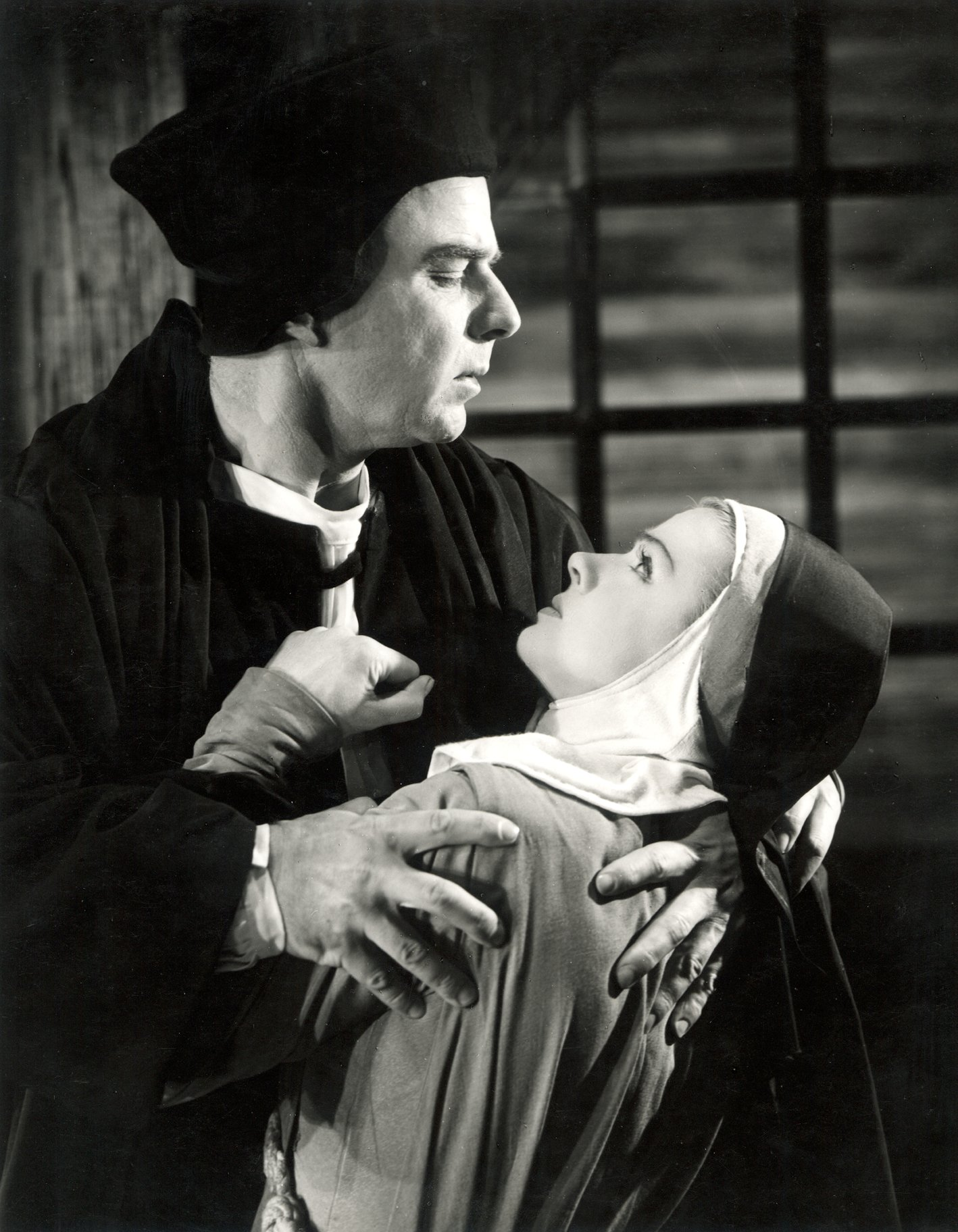 A man holds onto a young nun.