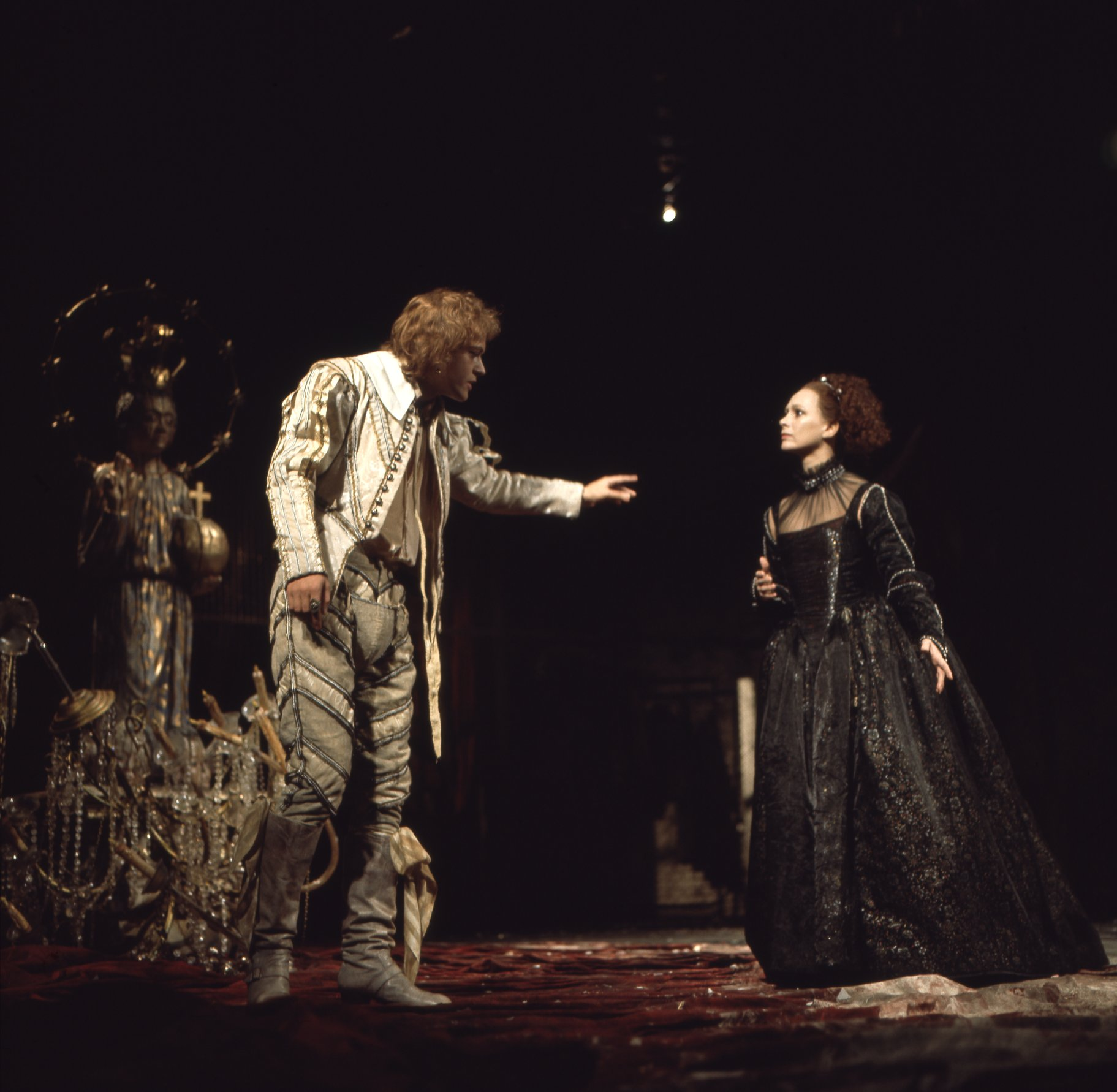 A man in all white talks to a woman in a black gown.