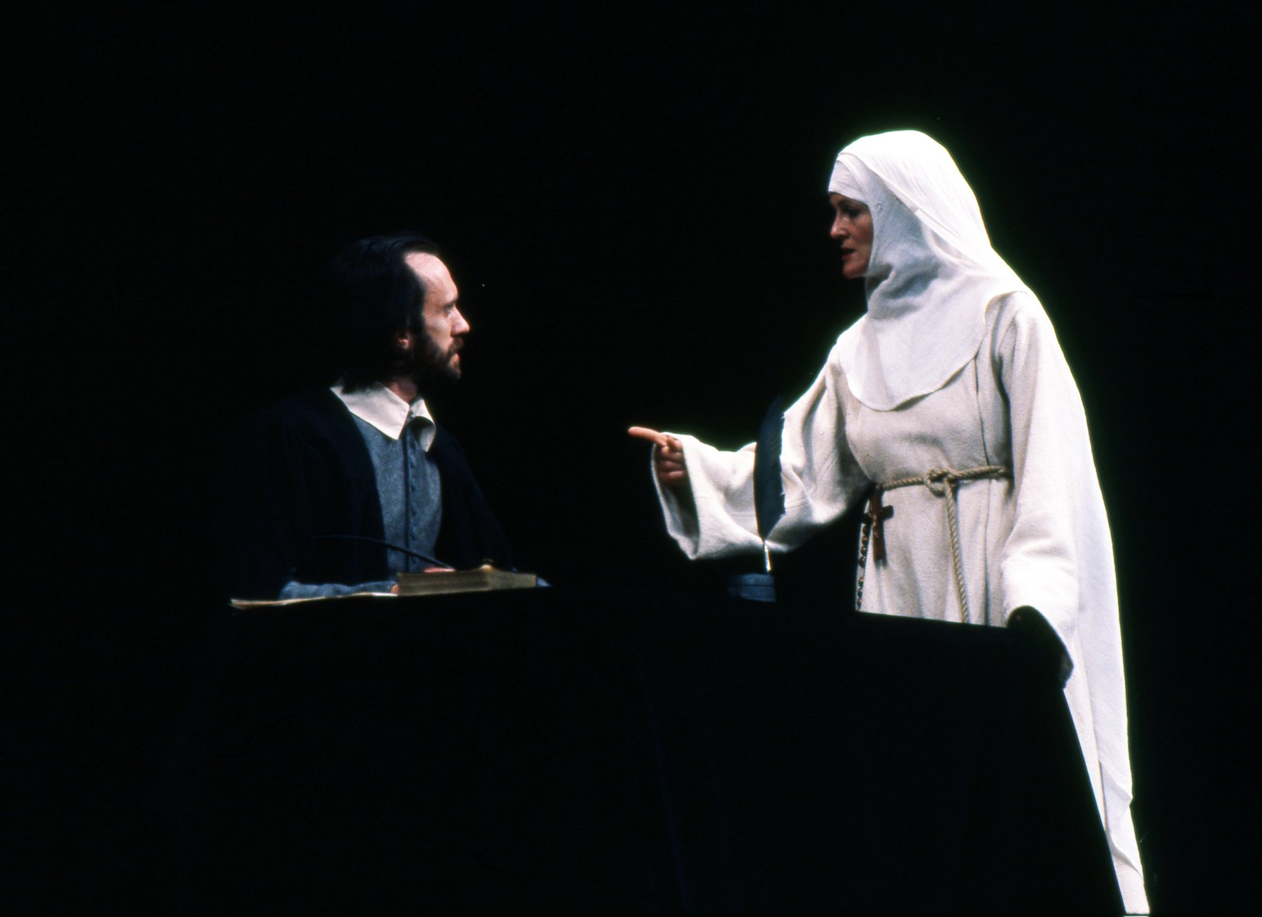 A nun points a finger at a bearded man.