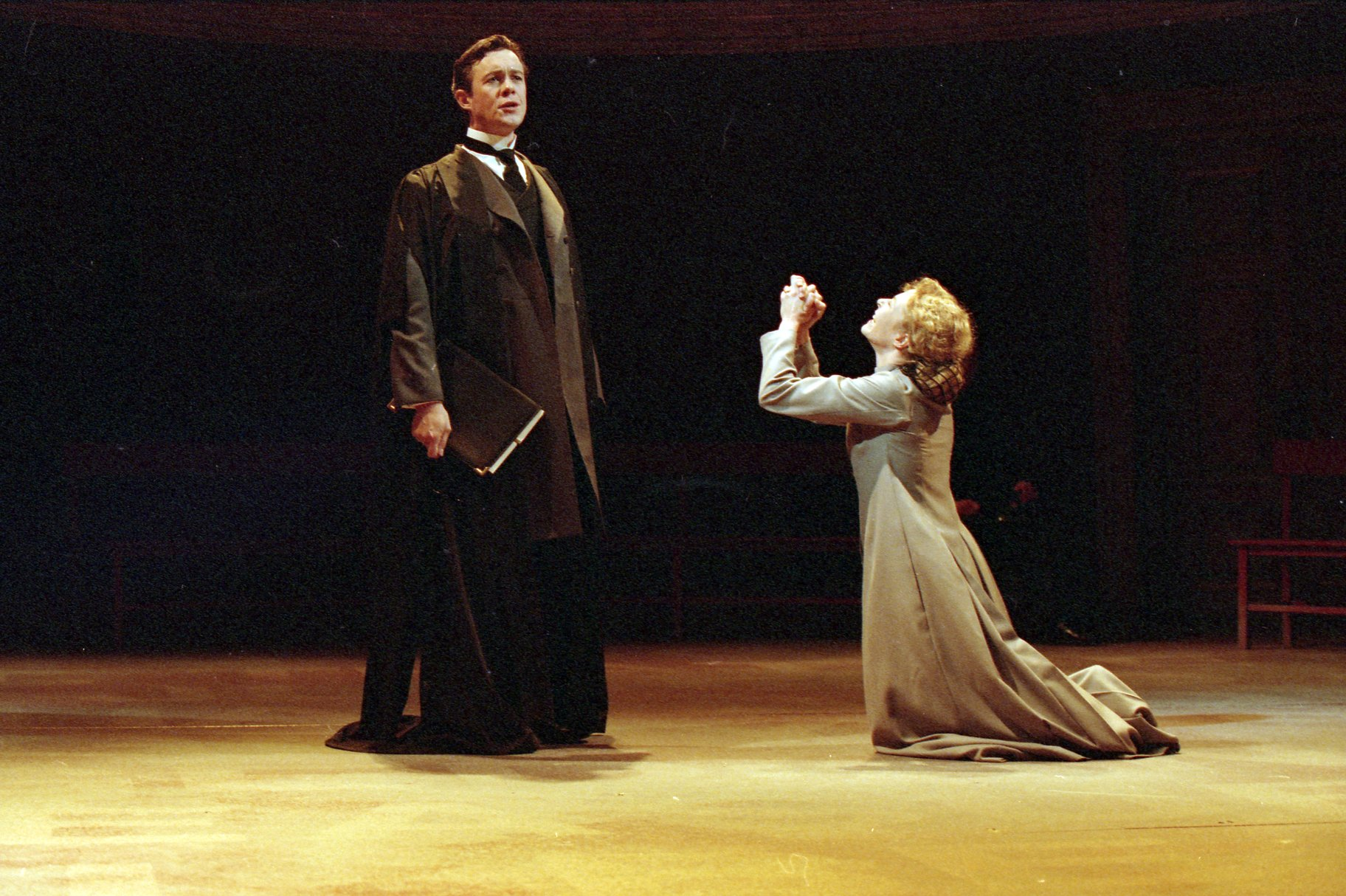 A woman pleads on her knees to a man in black scholar's robes.