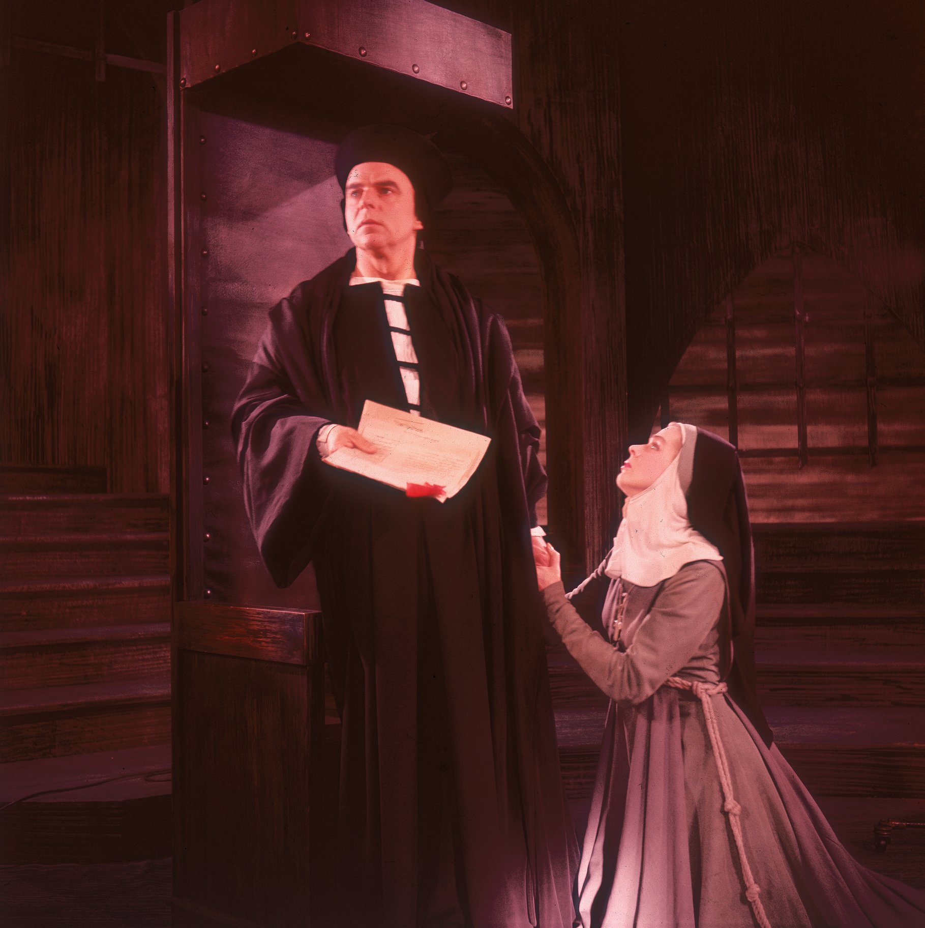 A nun pleads on her knees to an older man.