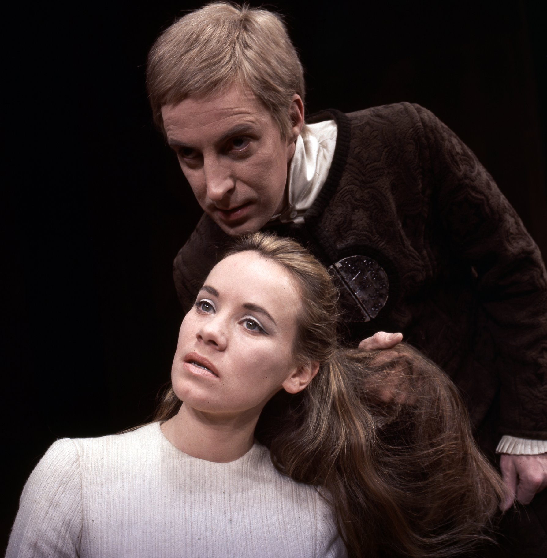 A man leans over a woman, pulling at her hair.