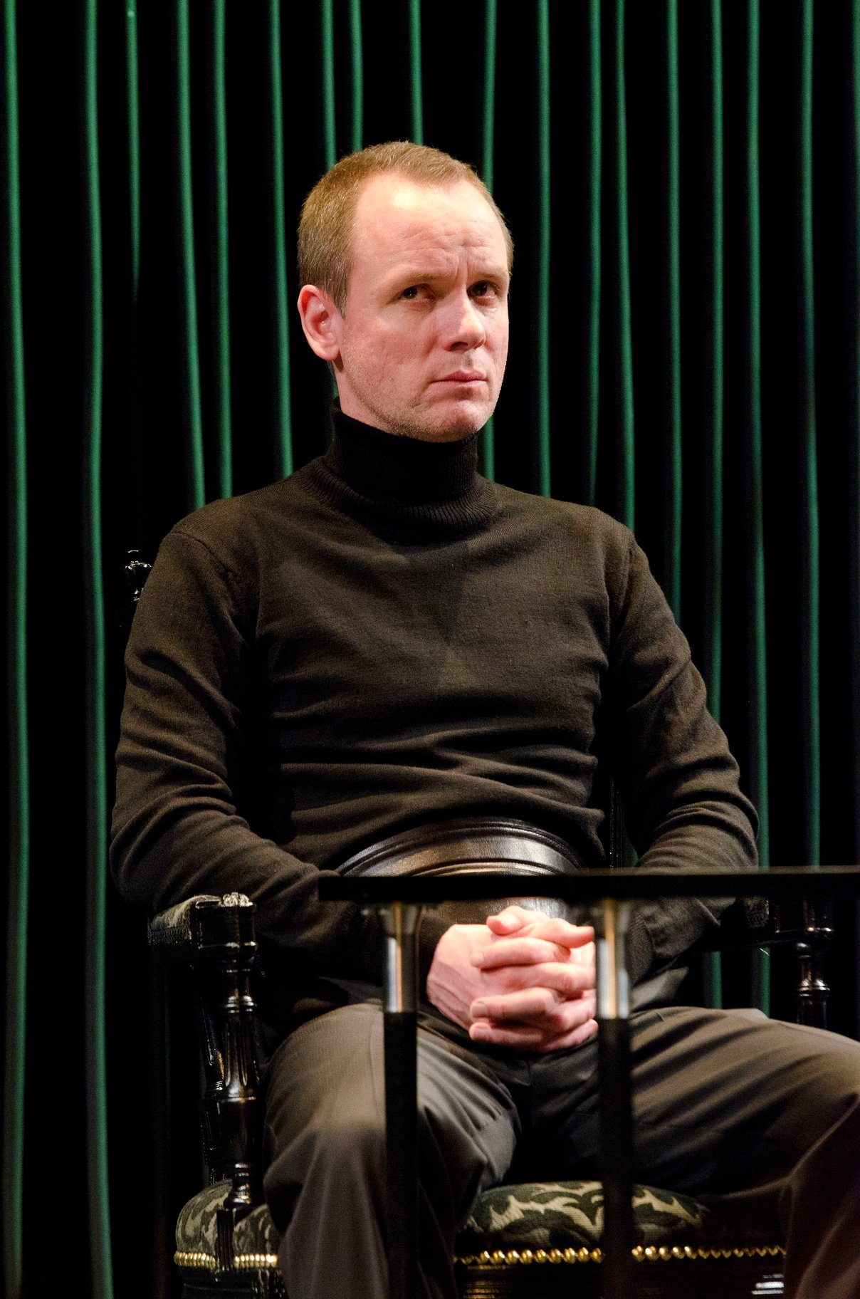A man in black polo shirt and trousers.