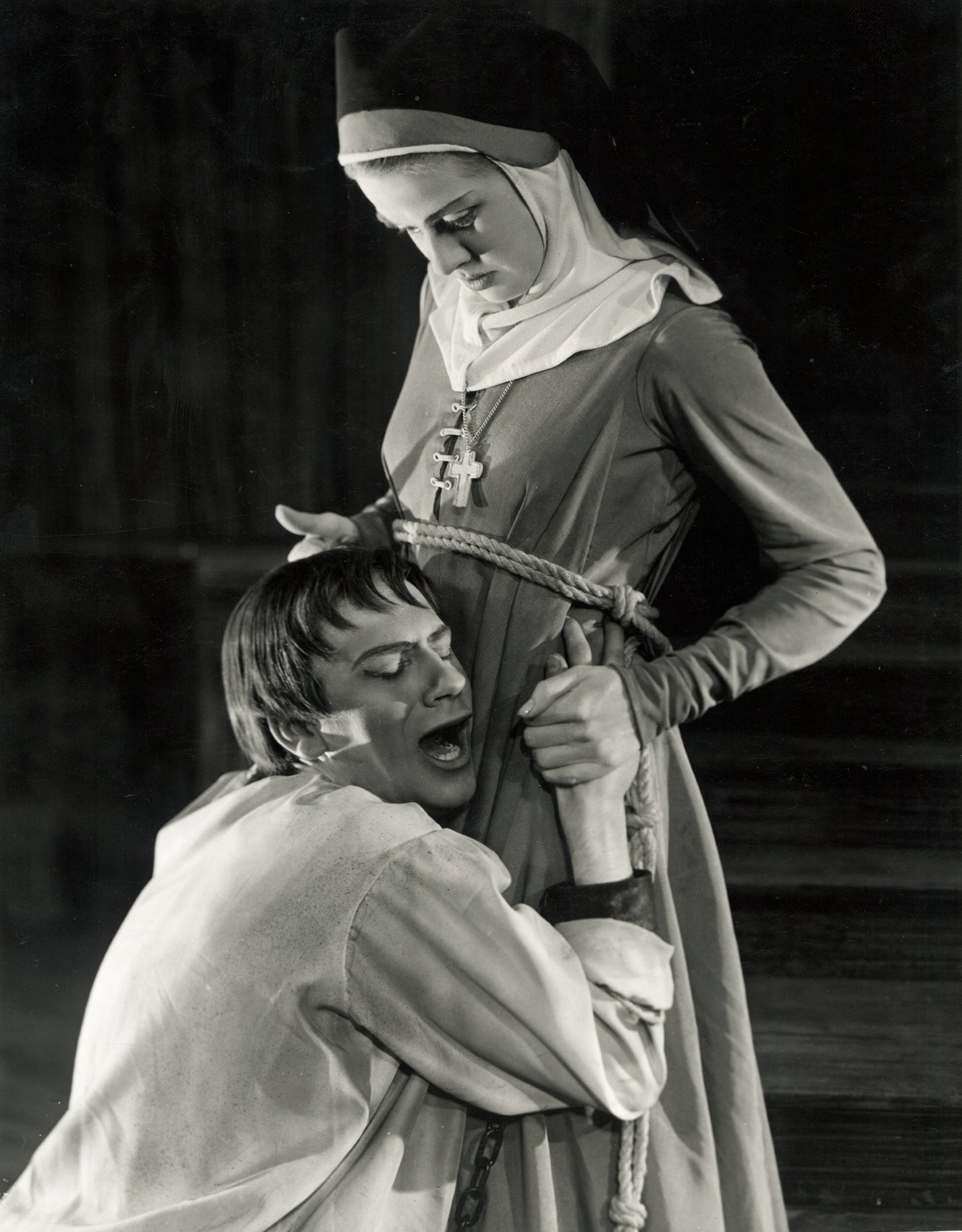 A man clings to the waist of a young nun.