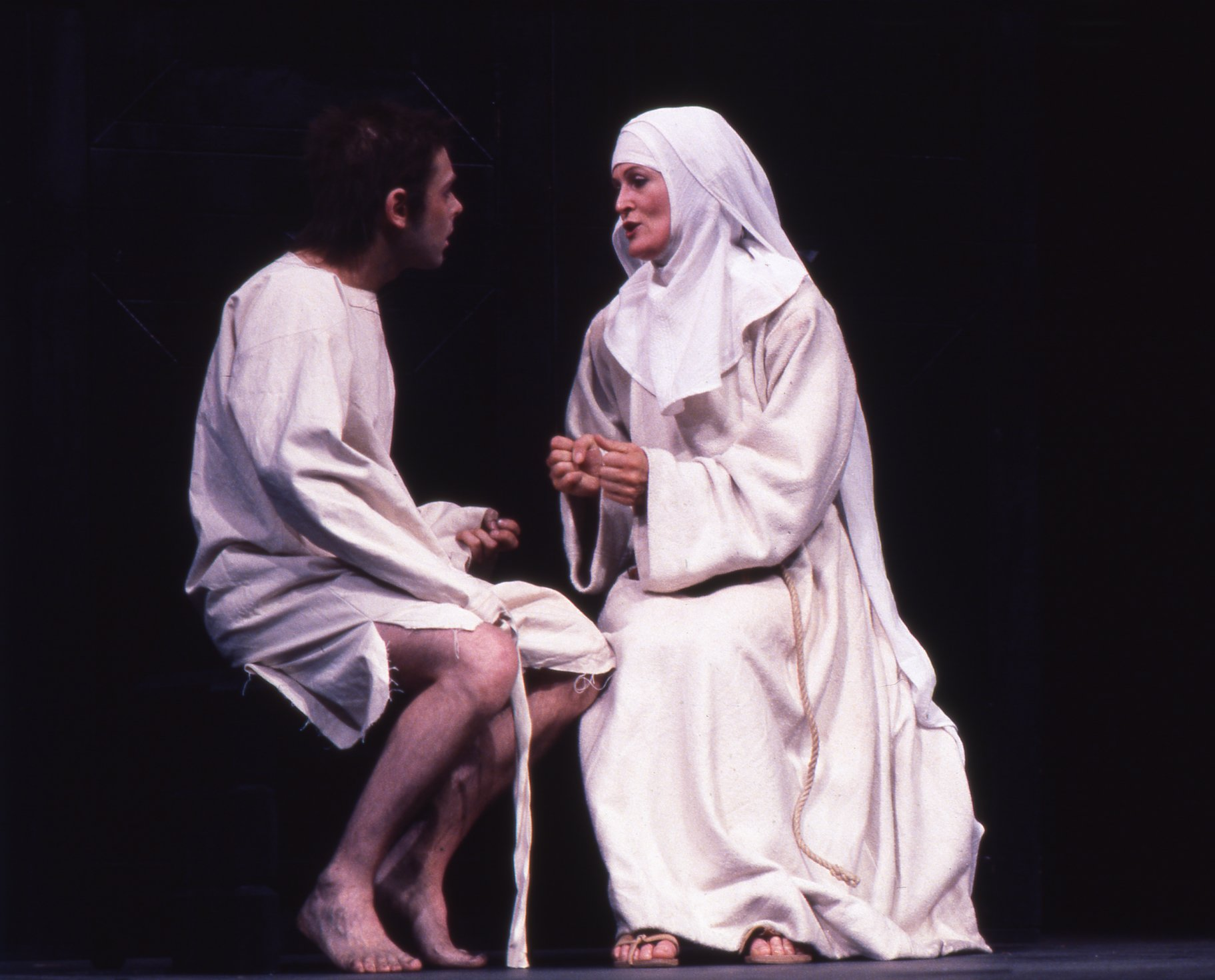 A nun talks to a prisoner in ragged white clothes.