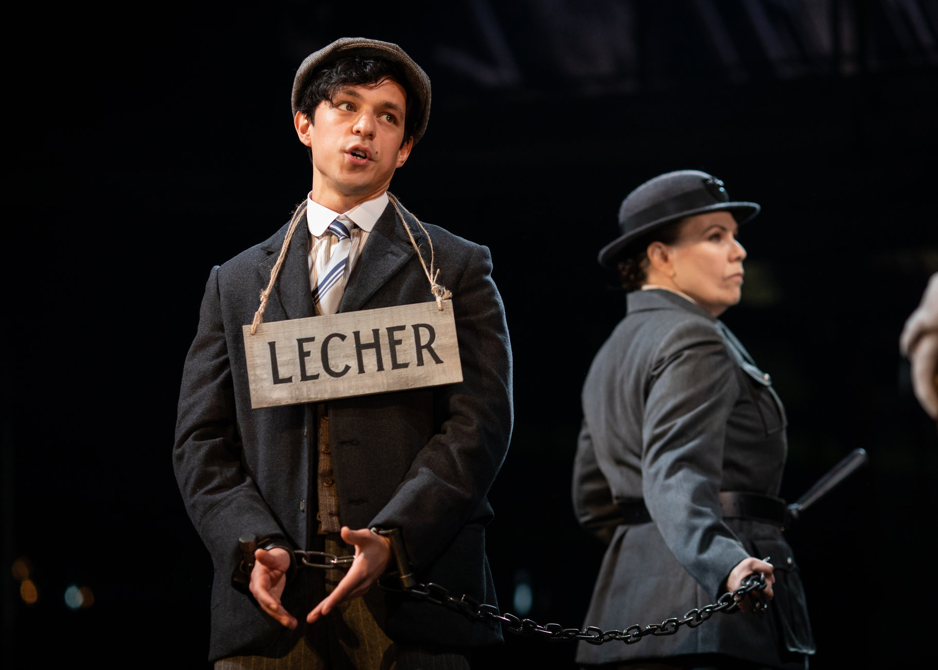 A man in chains with a sign around his neck saying 'Lecher'.