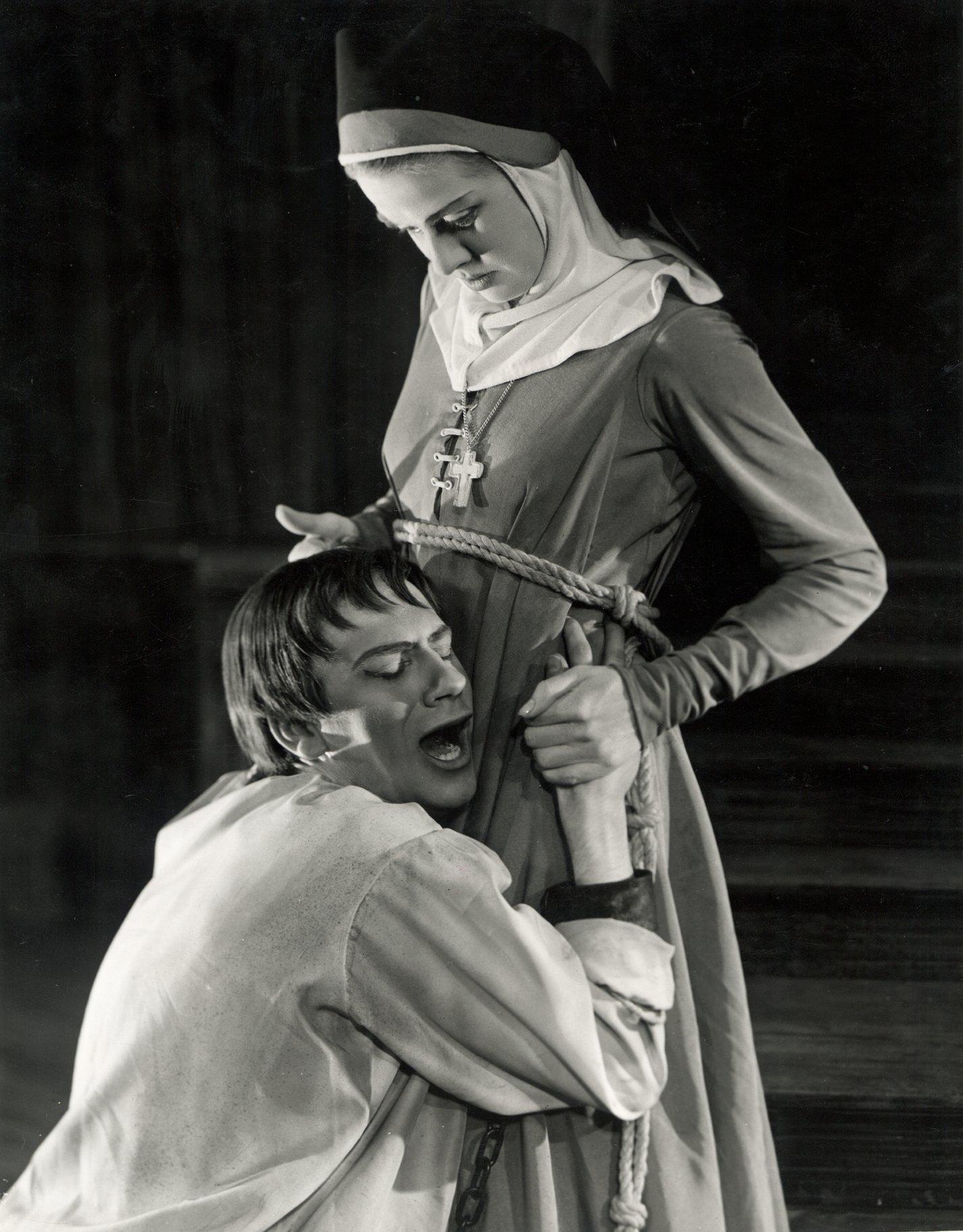 A man hugs tightly to a nun's waist.