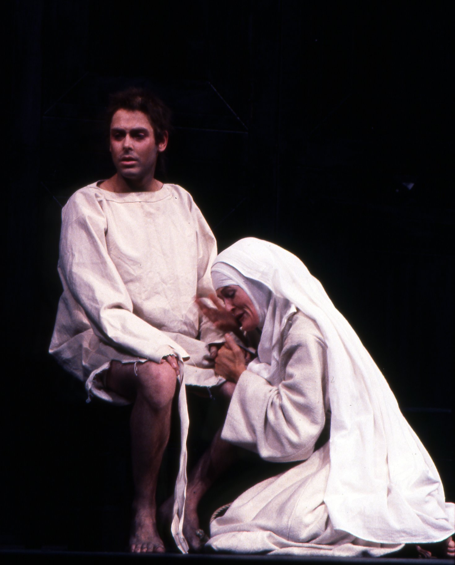 A nun kneels by a man in white rags.