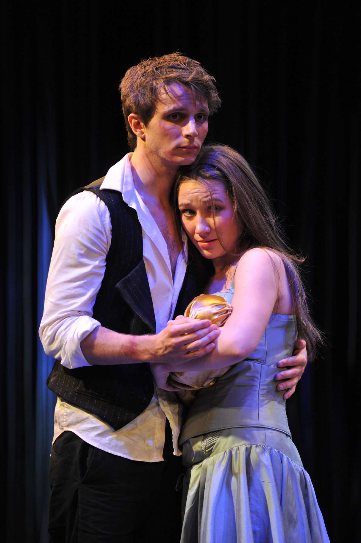 A young man hugs a woman holding a baby.