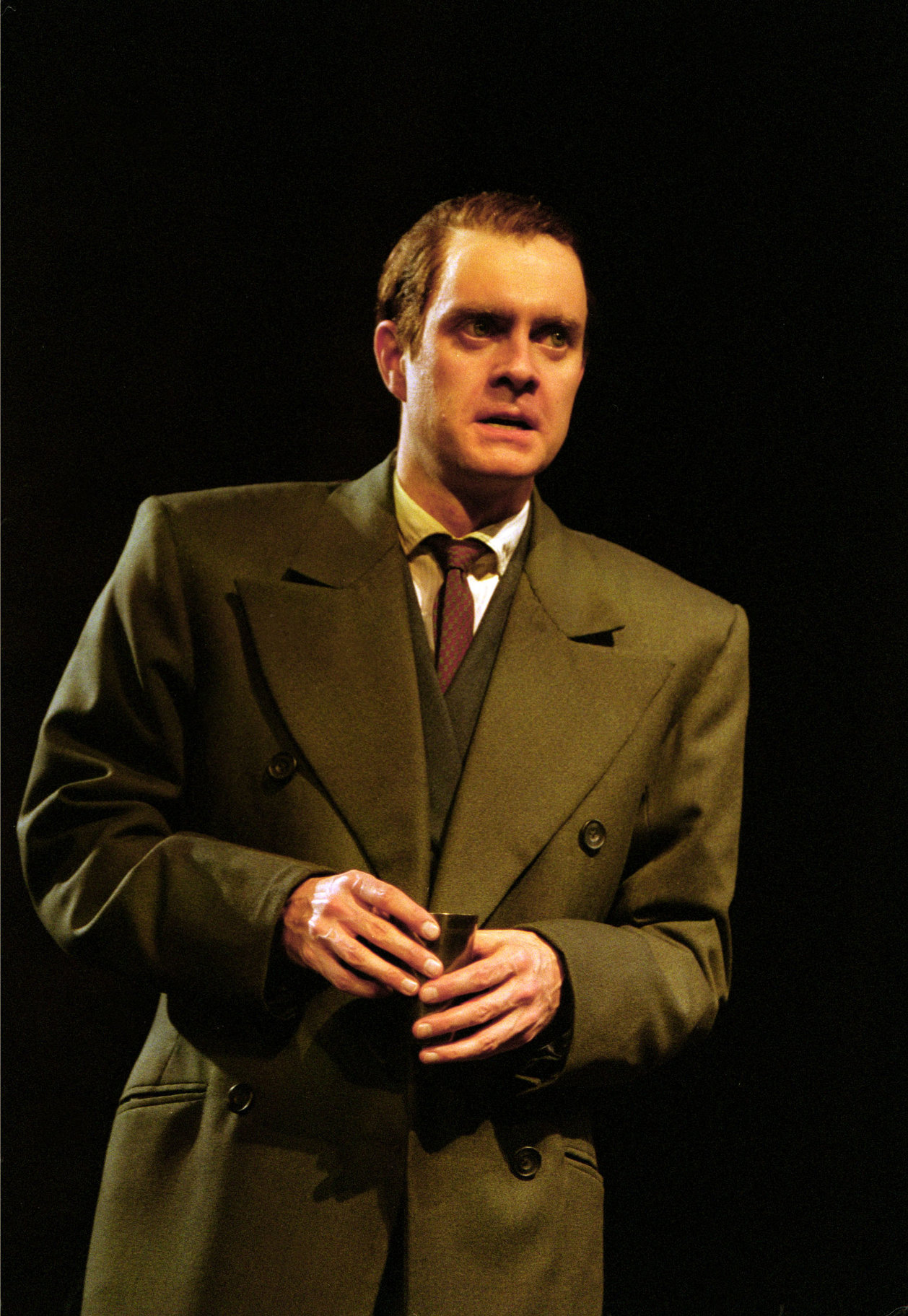 A man in a suit and long green coat.