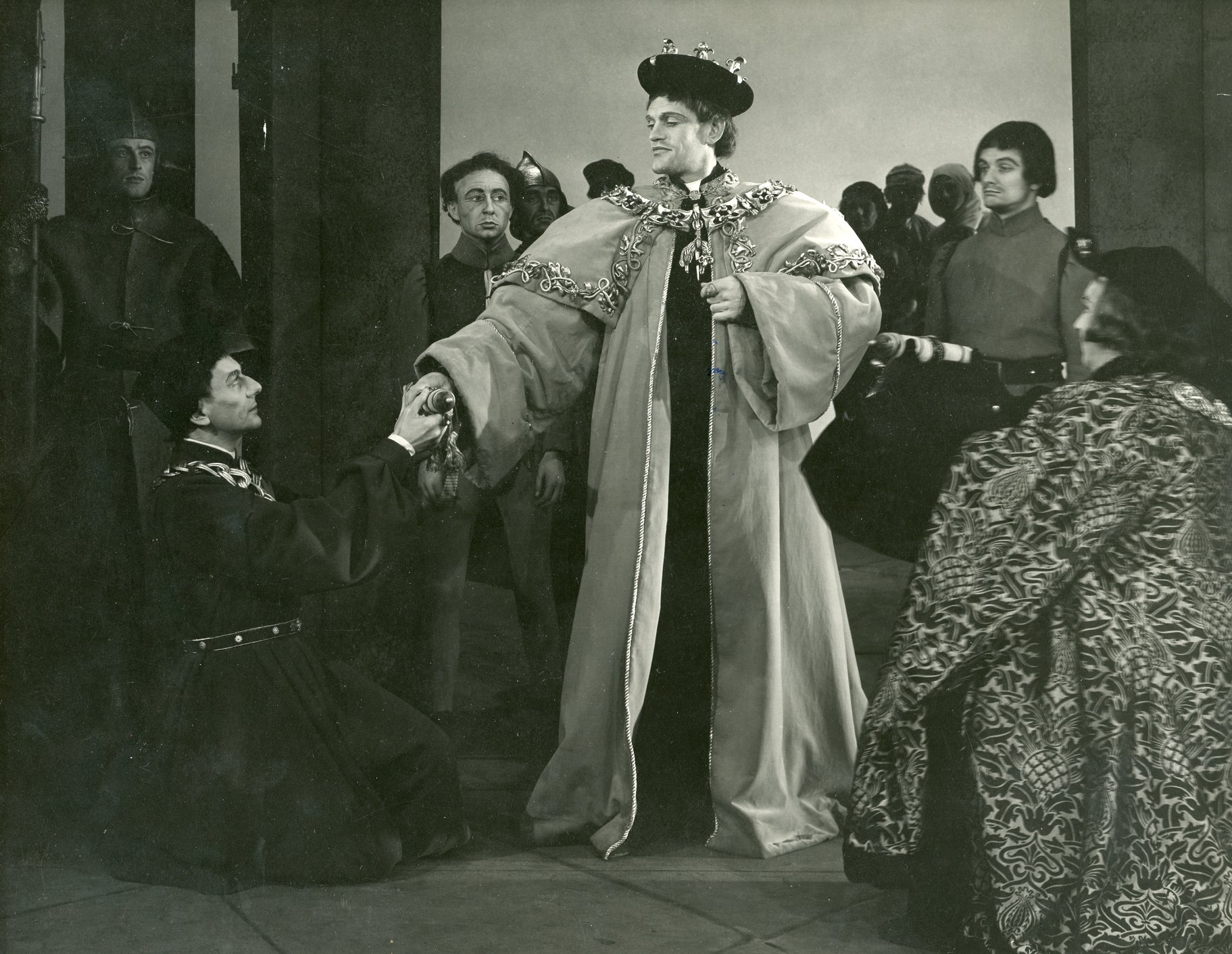 A man in long robes and gold chains hold court.