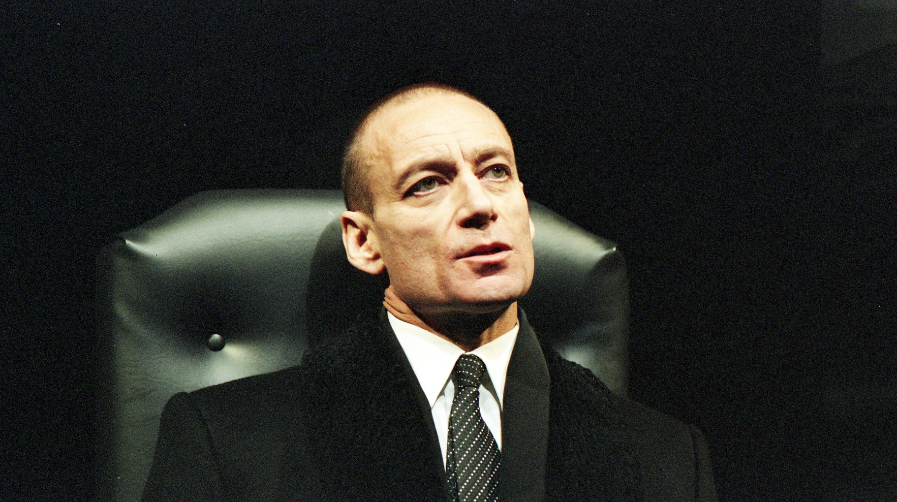 A man in a dark suit sits in a leather chair.