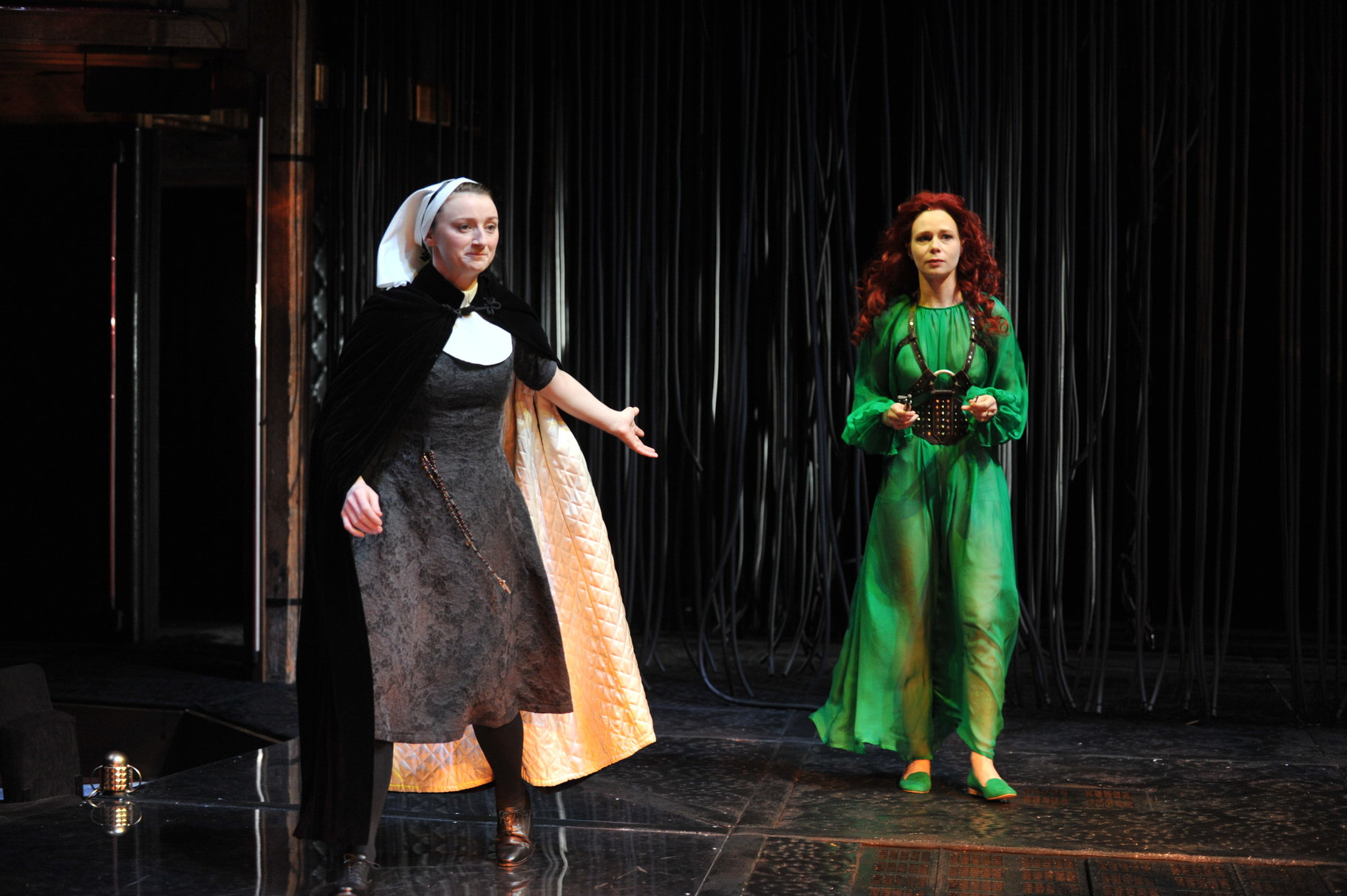 A nun gestures towards a woman in a sheer green dress.