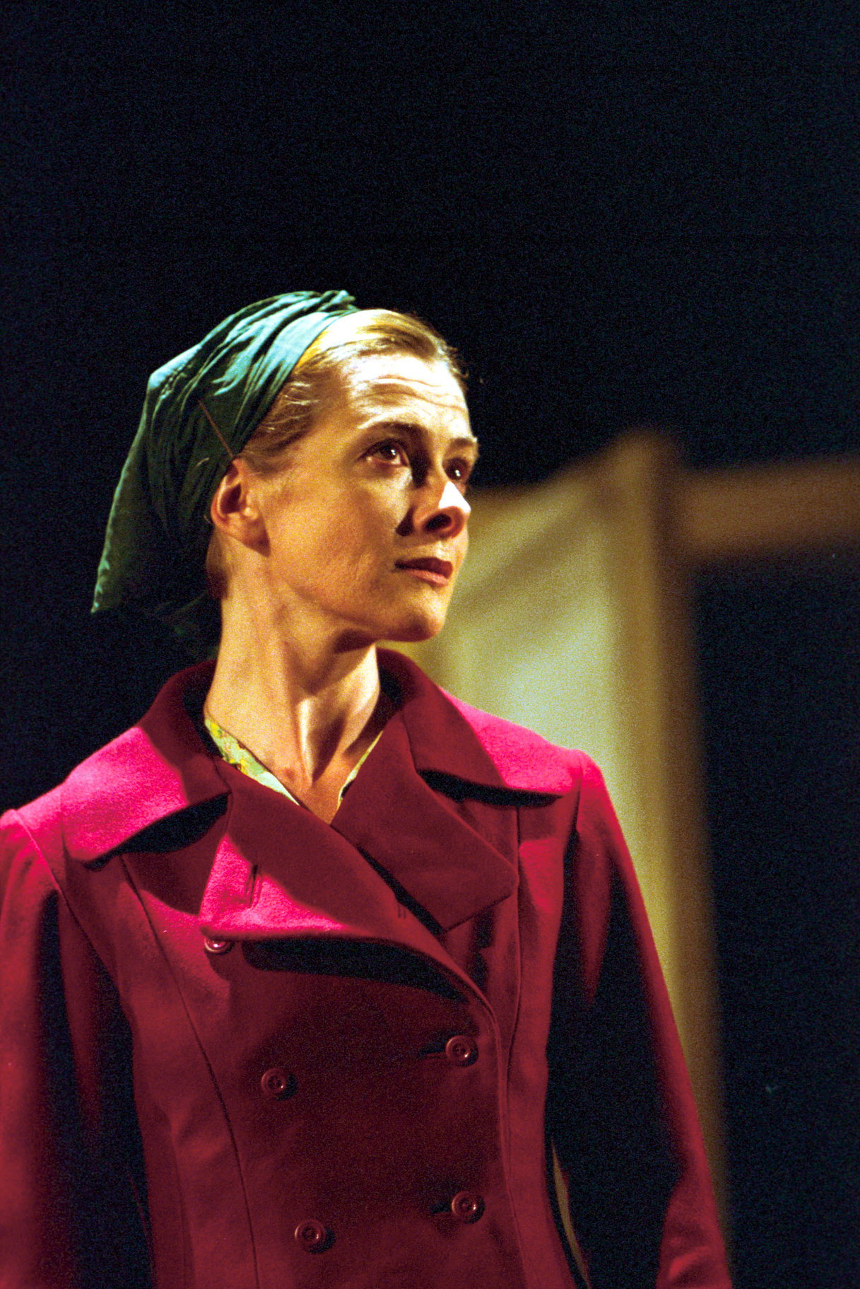 A woman in a burgundy coat and green head scarf.